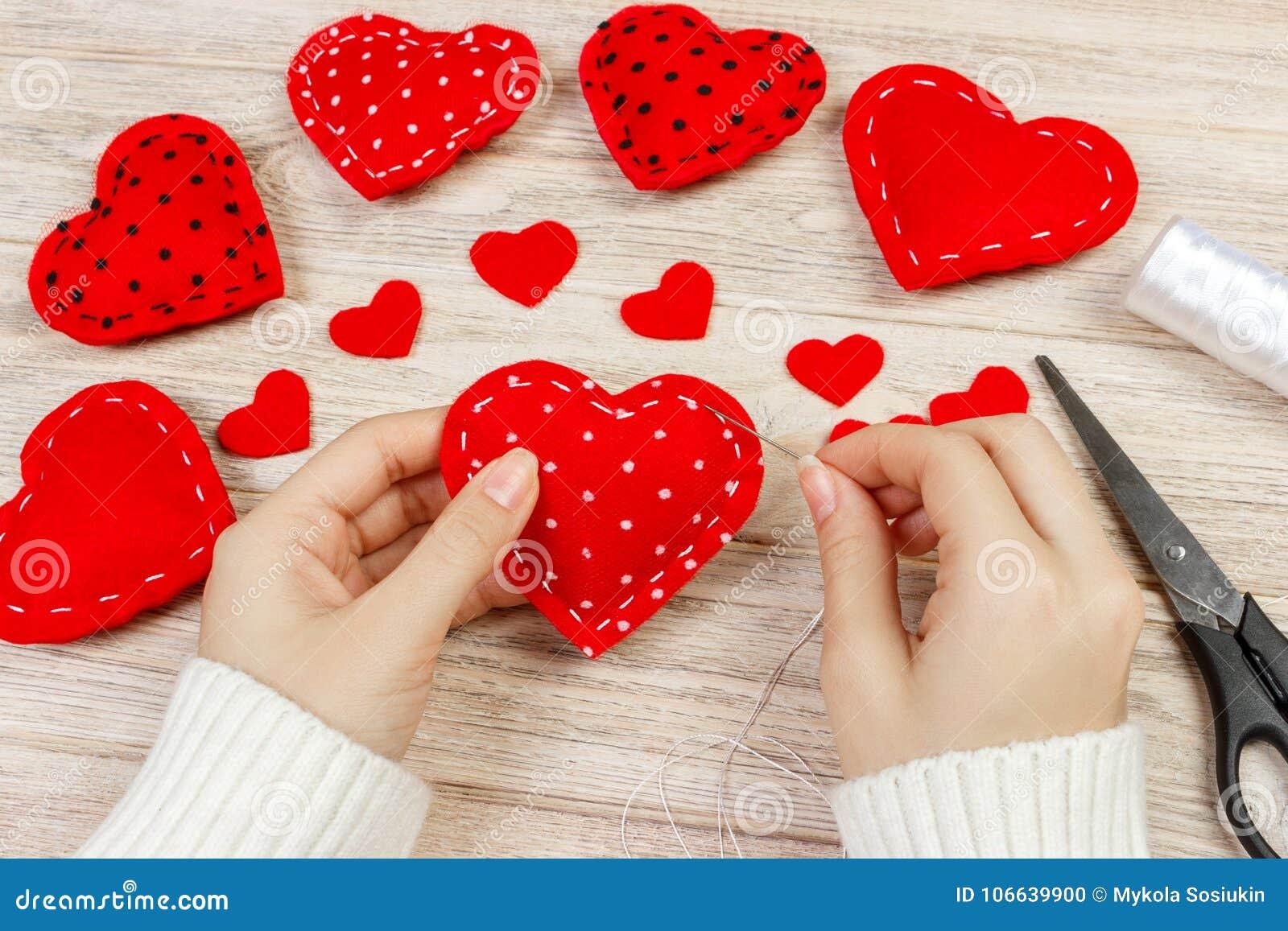 Frau, die rotes Herz auf Holztisch schafft Geschenk für St.-Valentinsgruß ` s Tag handgemacht