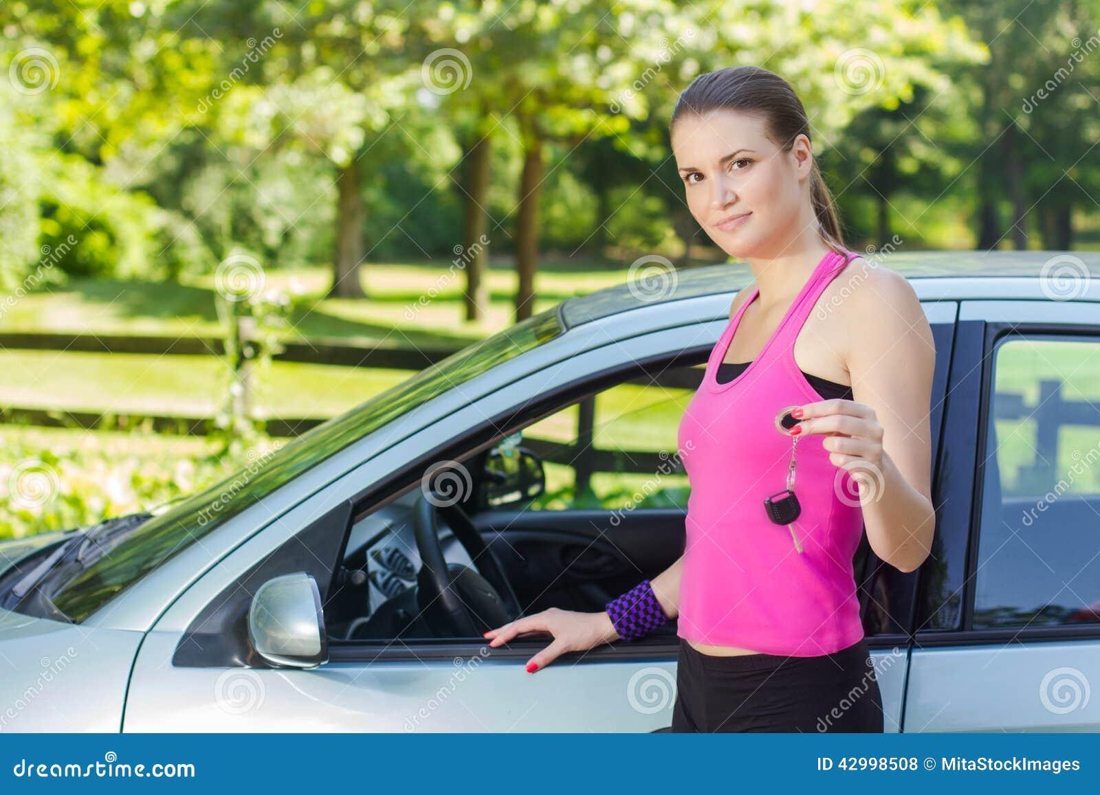 Frau, die Schlüssel des Neuwagens zeigt