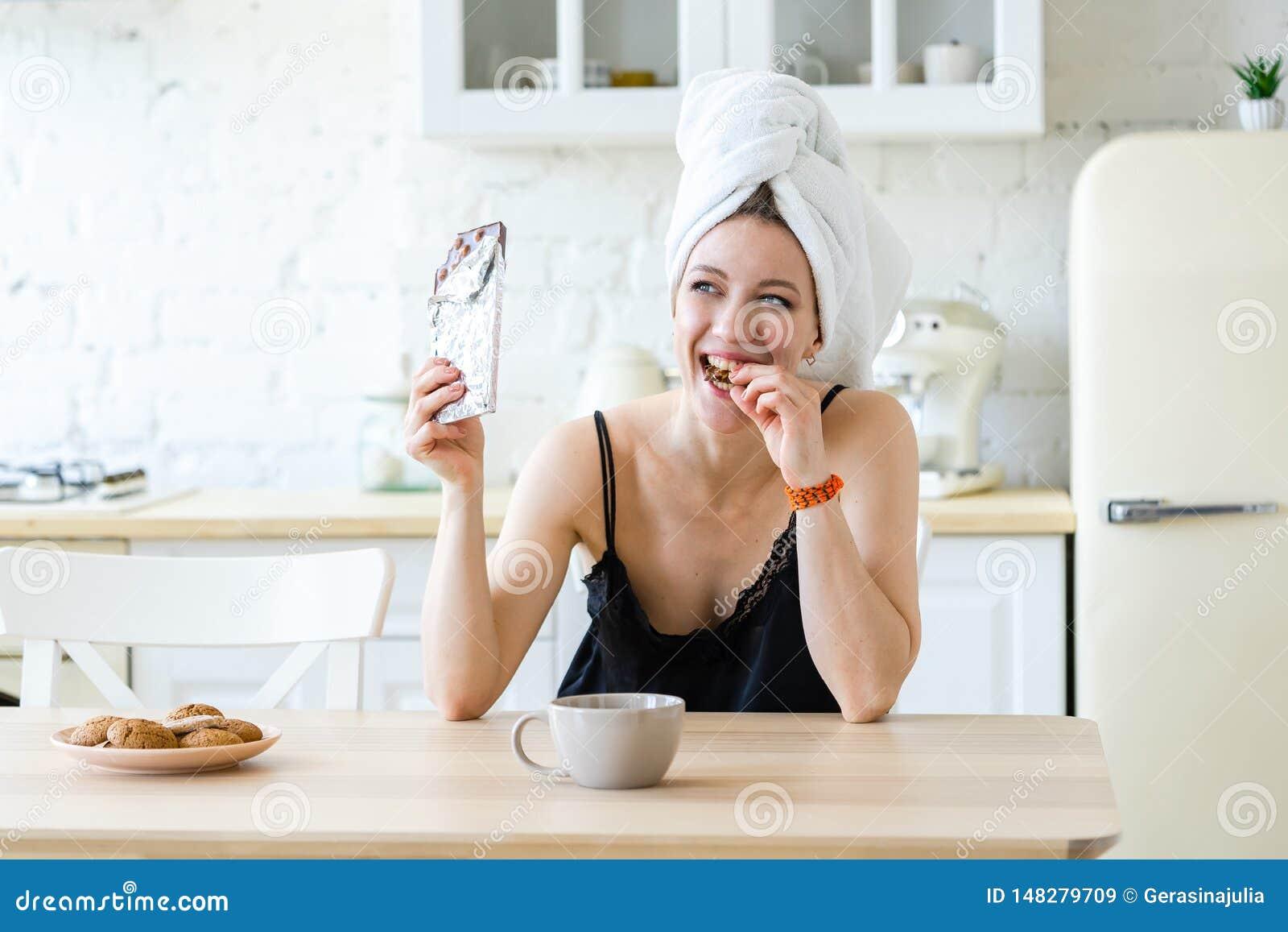 Frau, die Schokolade isst und nachdem Di?t genie?t, gehalten worden ist Betr?germahlzeit