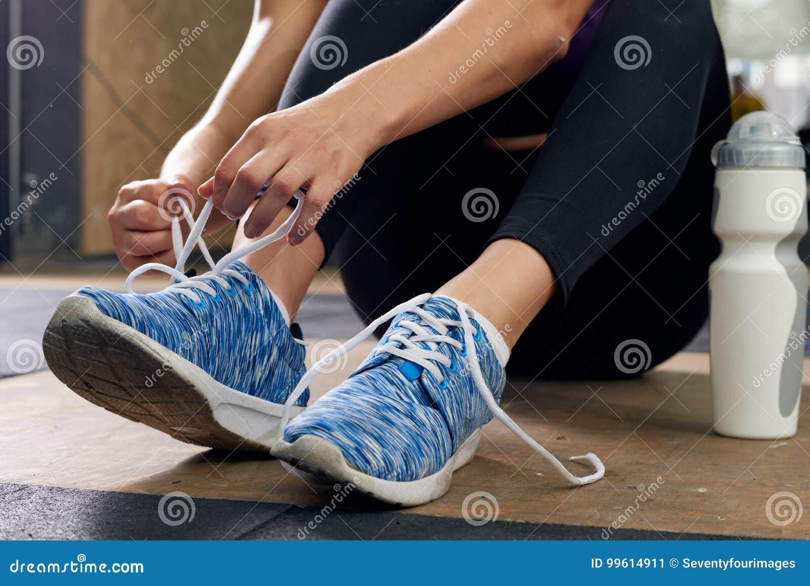 Frau, Die Sport Schuhe In Der Turnhalle Bindet Stockbild