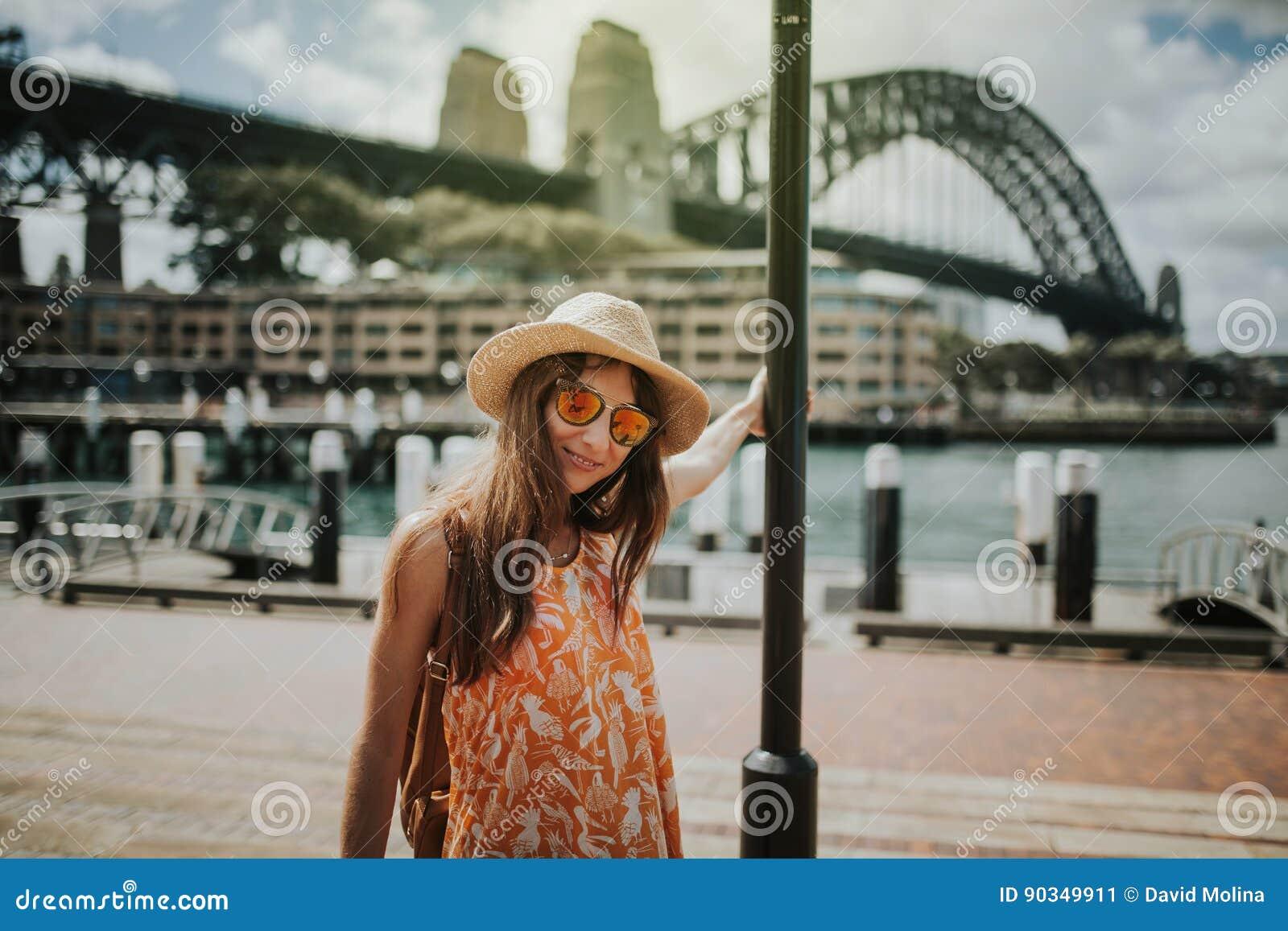 Frau, die in Sydney-Stadt mit Hafen-Brücke im Hintergrund aufwirft