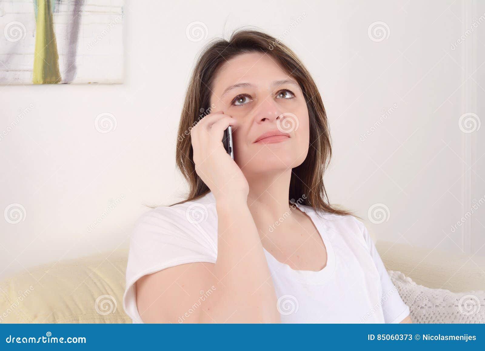 Frau, die am Telefon sitzt auf dem Sofa spricht