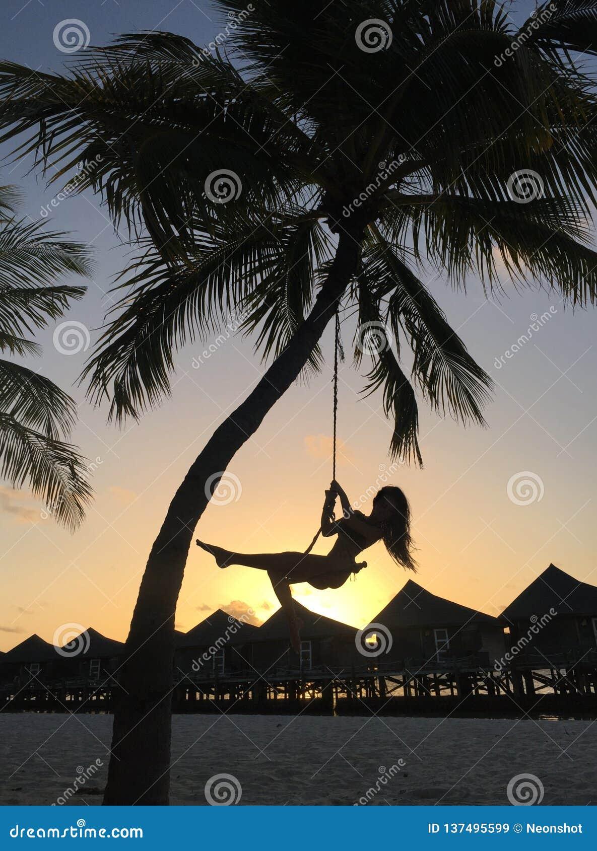 Frau, die am tropischen Strand schwingt