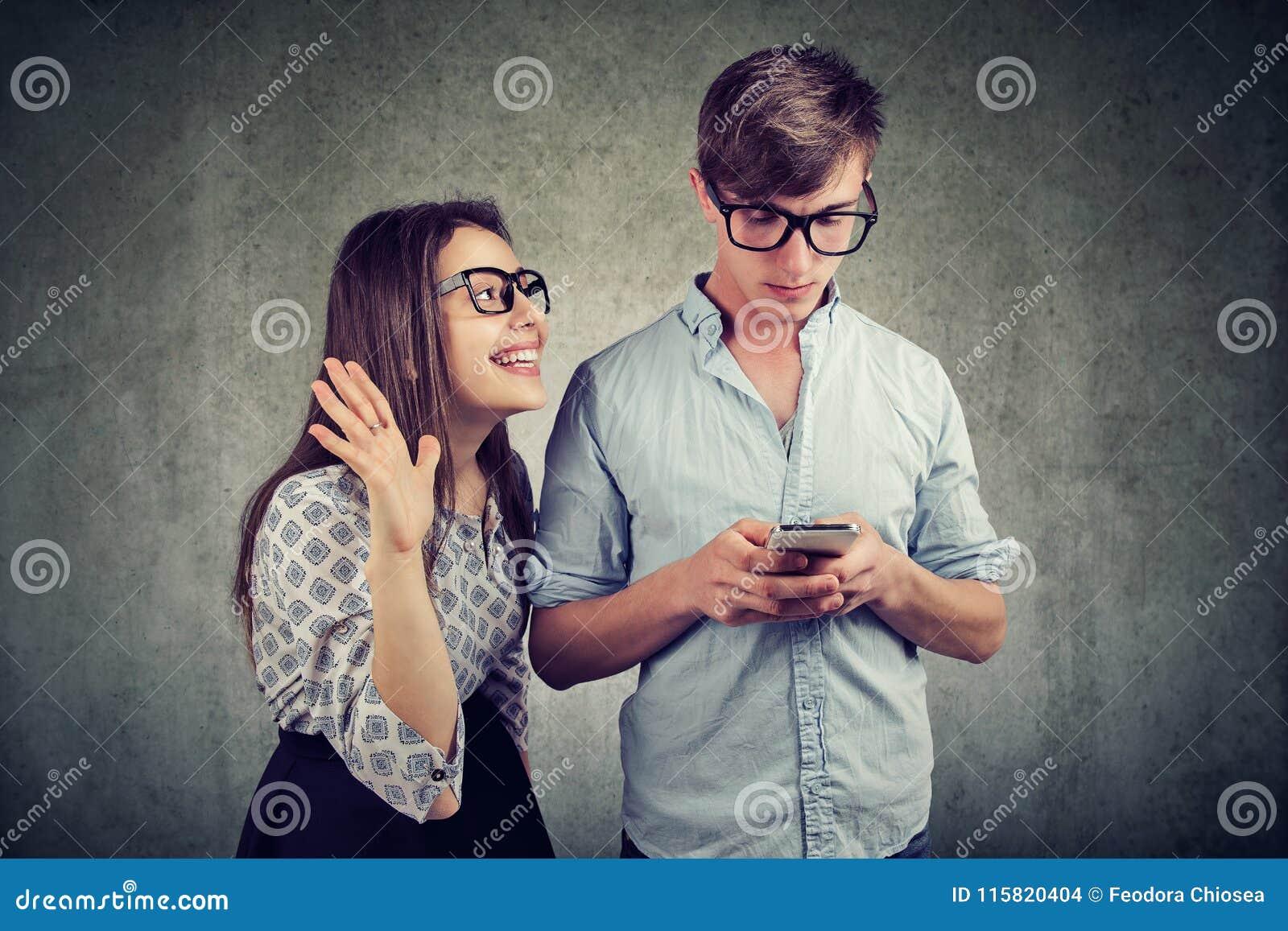 Frau, die versucht, Aufmerksamkeit eines gutaussehenden Mannes zu holen ignoriert sie unter Verwendung eines Smartphone