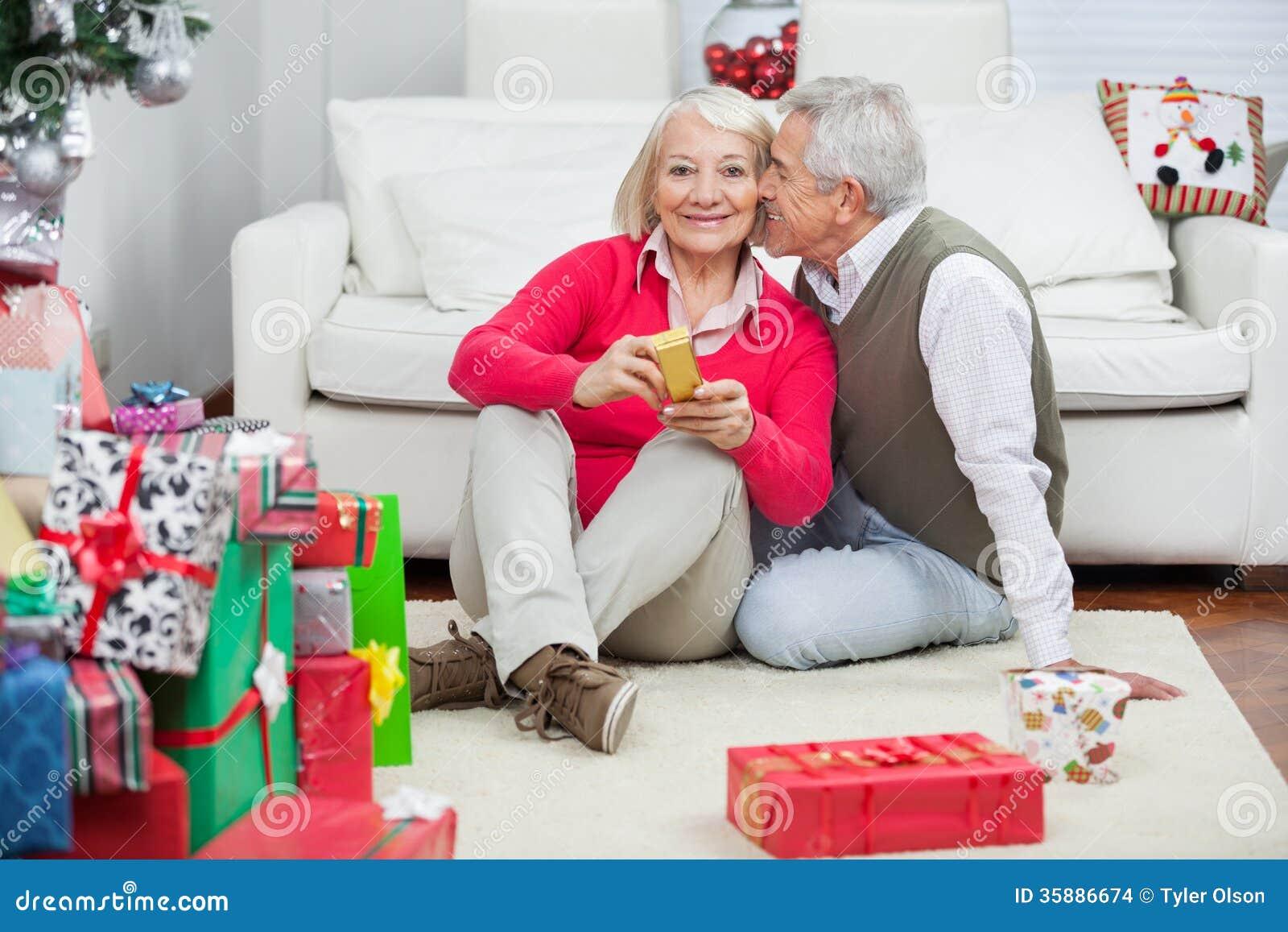 Frau, Die Weihnachtsgeschenk Während Mann Ungefähr Zu Hält Stockfoto ...