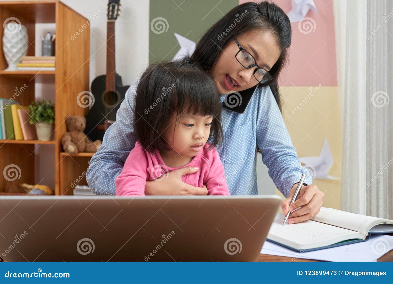 Frau, die zu Hause mit kleinem Mädchen arbeitet