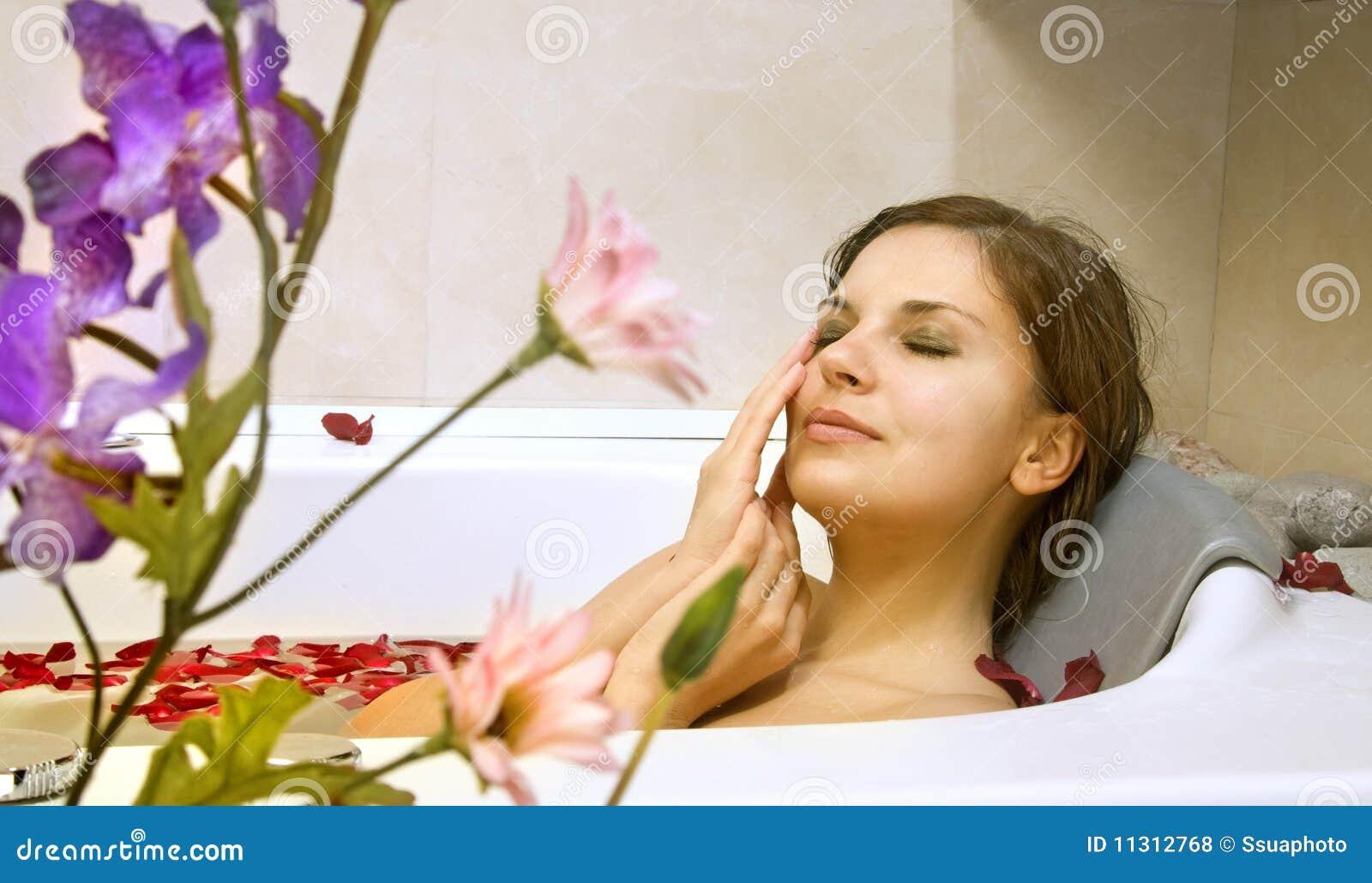 Frau in einem Bad mit den Steigenblumenblättern