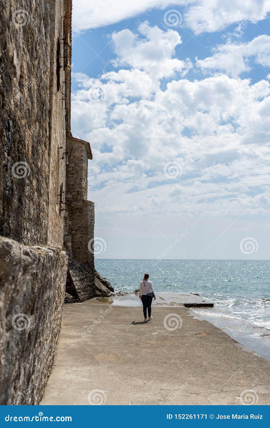 Frau in einem Steinhafen in einer alten Stadt des adriatischen Meeres Wasser in einem Felsenpier und in einer mittelalterlichen W