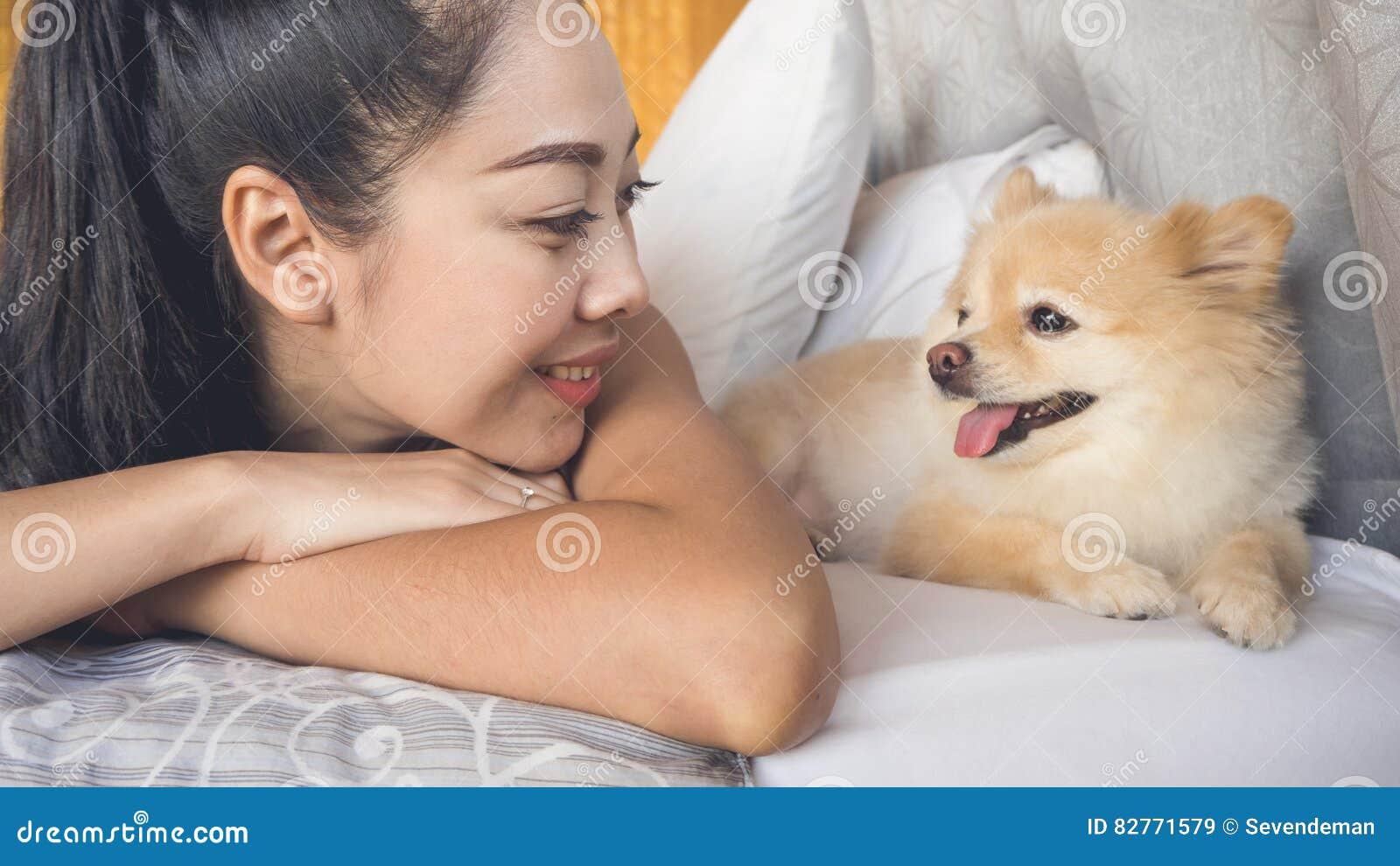 Frau Entspannen Sich Mit Hund Im Schlafzimmer Stockbild - Bild von ...