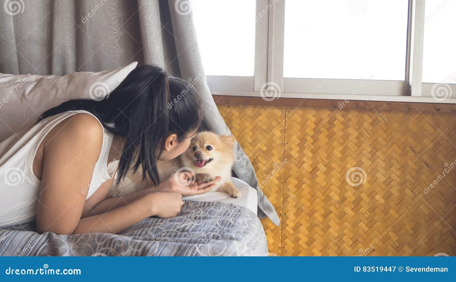 Frau Entspannen Sich Mit Hund Im Schlafzimmer Stockbild ...