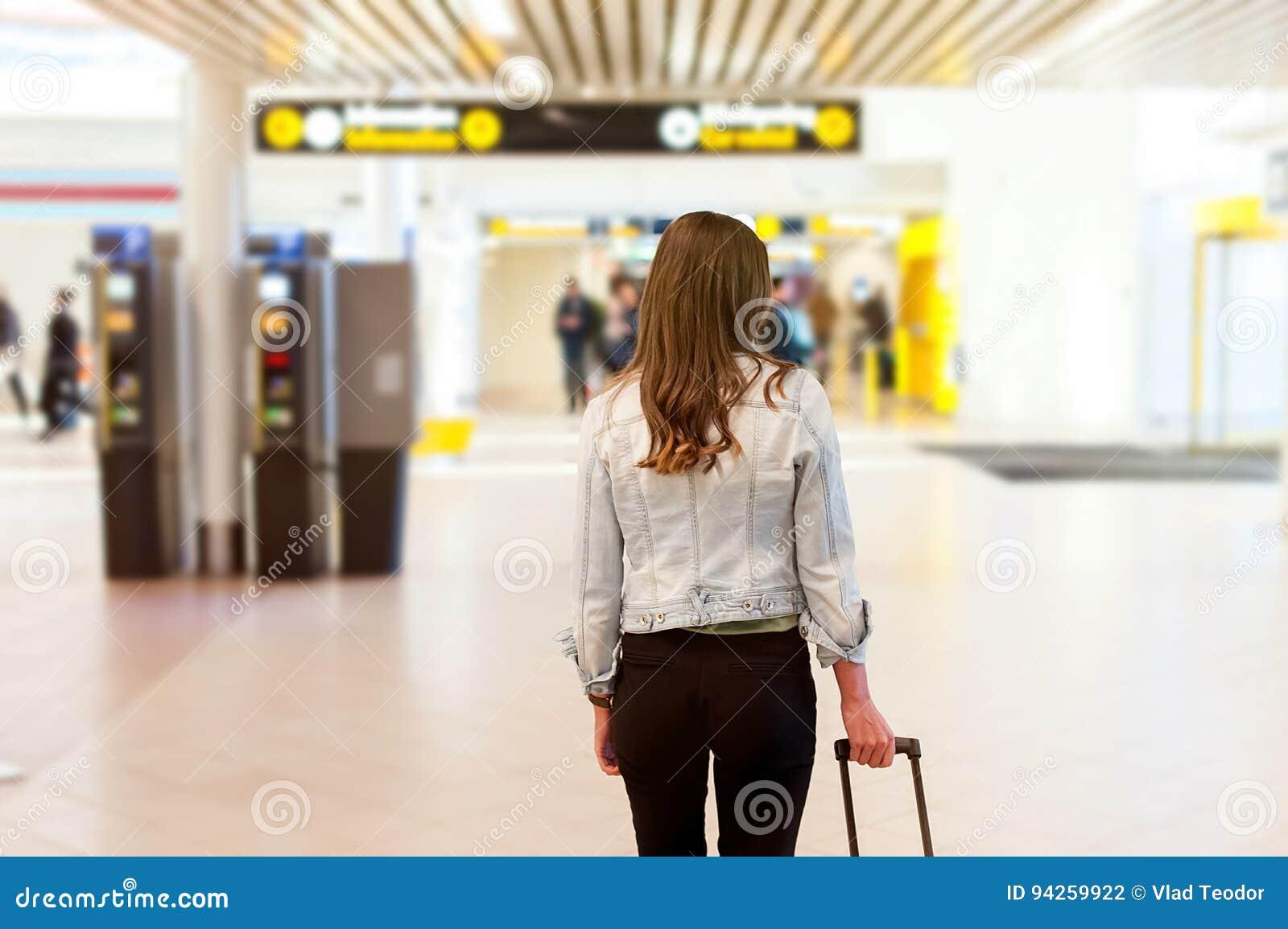 Frau am Flughafen, ihre Laufkatzentasche tragend