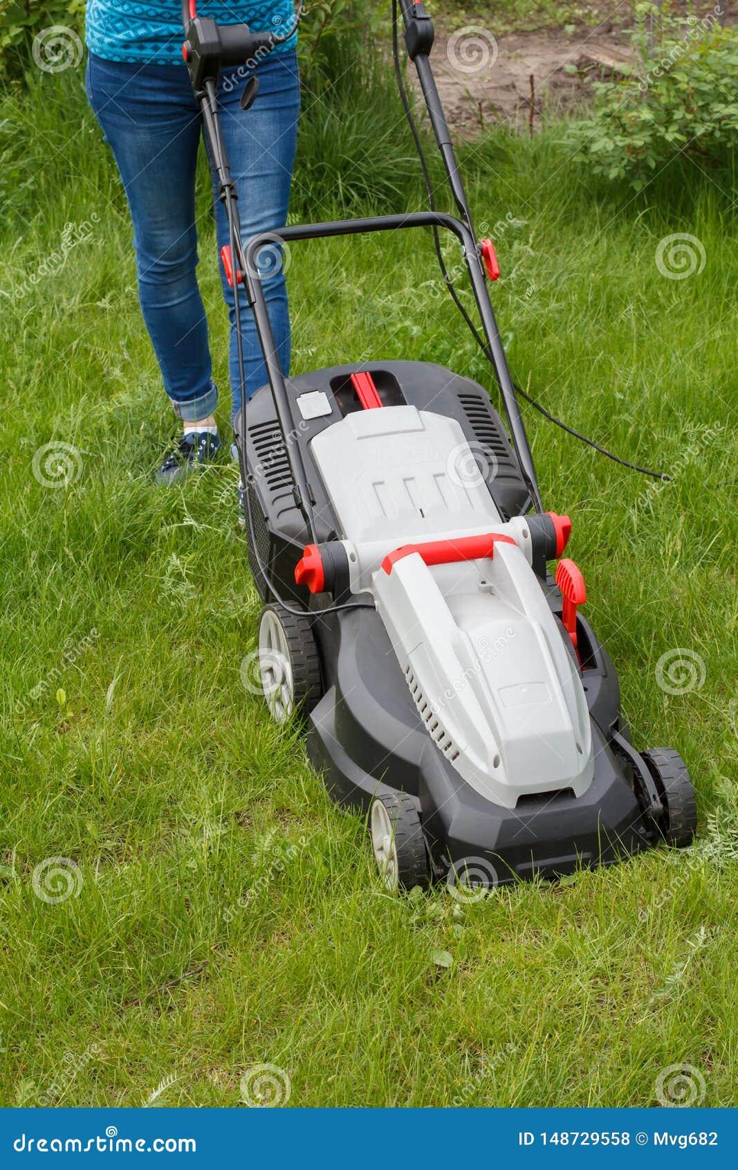 Frau funktioniert mit Rasenm?her im Garten