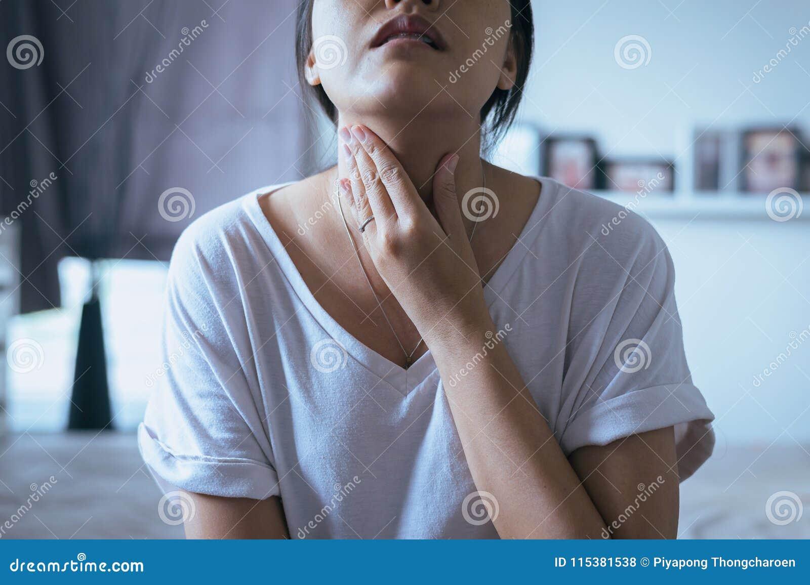 Frau haben Halsschmerzen, weiblichen rührenden Hals mit der Hand, Gesundheitswesen-Konzepte