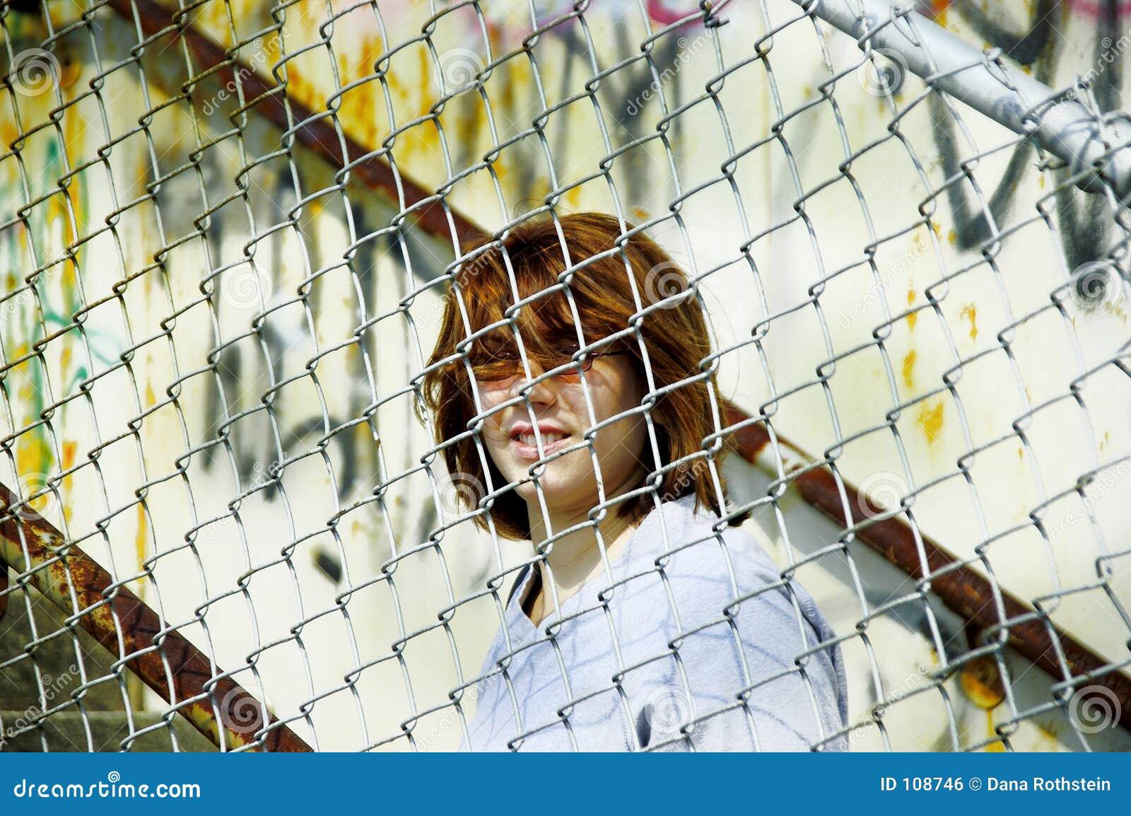 Frau hinter Zaun