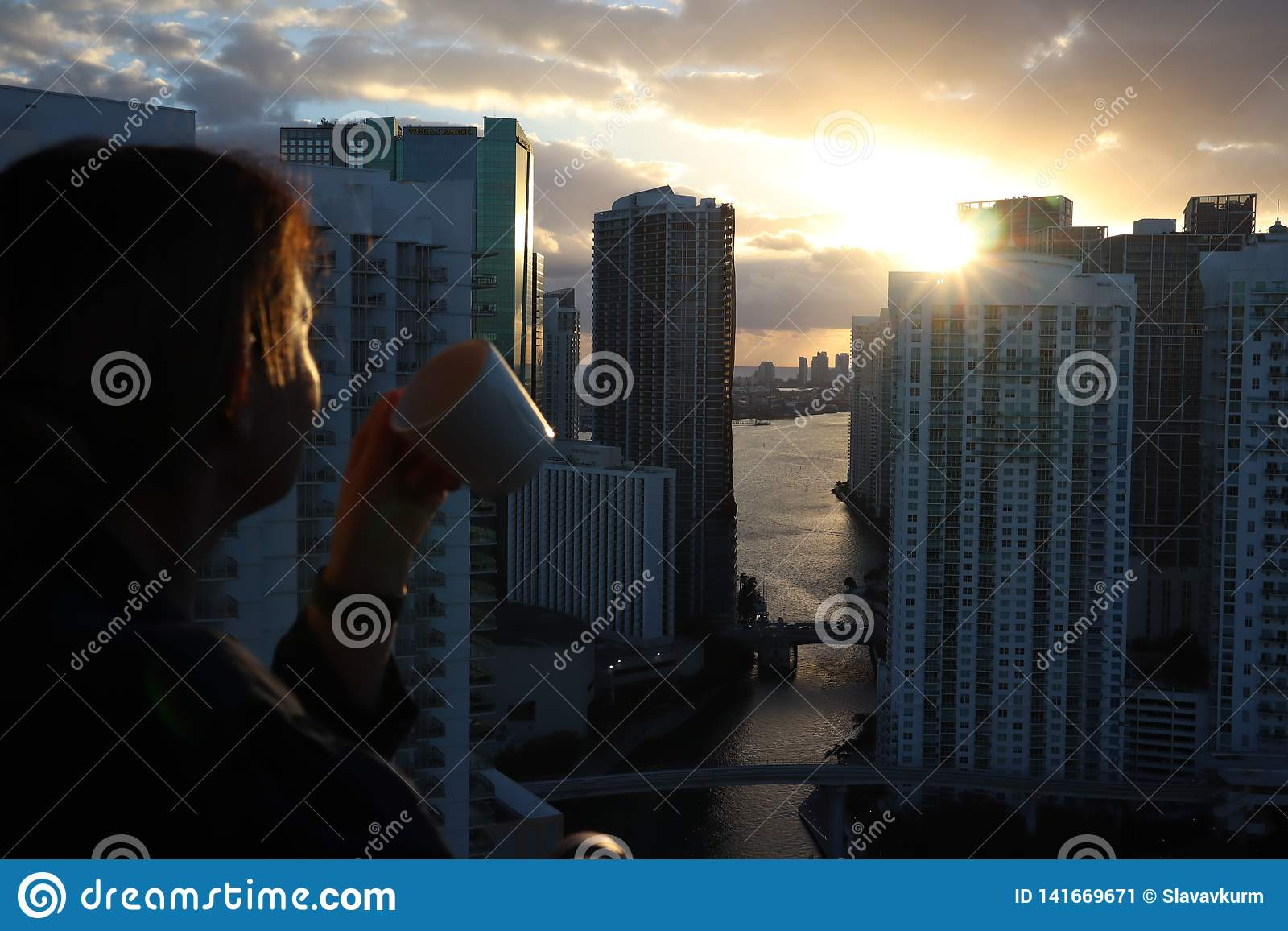 Frau im Bademantel ihren Morgenkaffee oder -tee auf einem im Stadtzentrum gelegenen Balkon trinkend Schöner Sonnenaufgang in im S