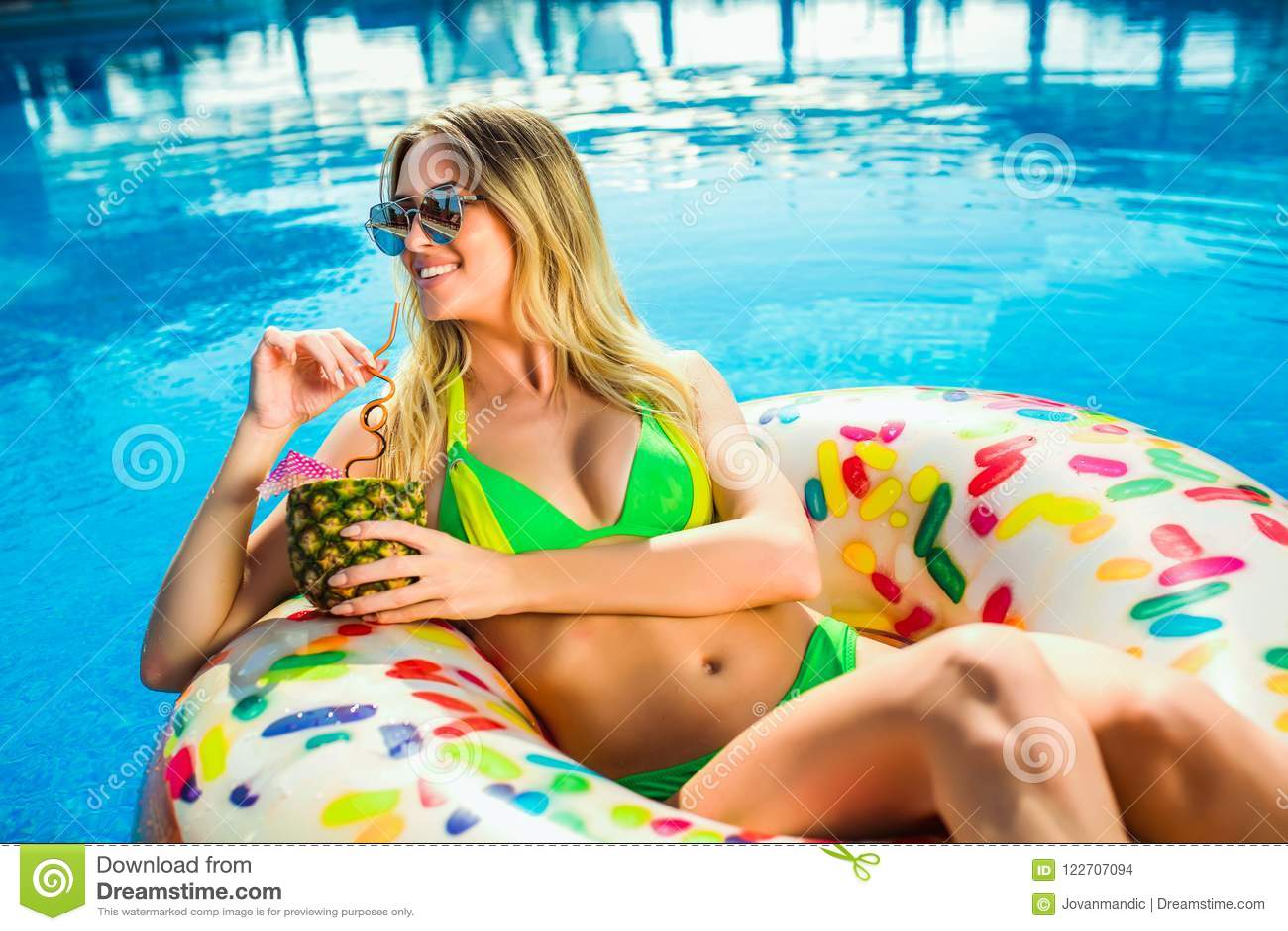Frau im Bikini auf der aufblasbaren Matratze im Swimmingpool