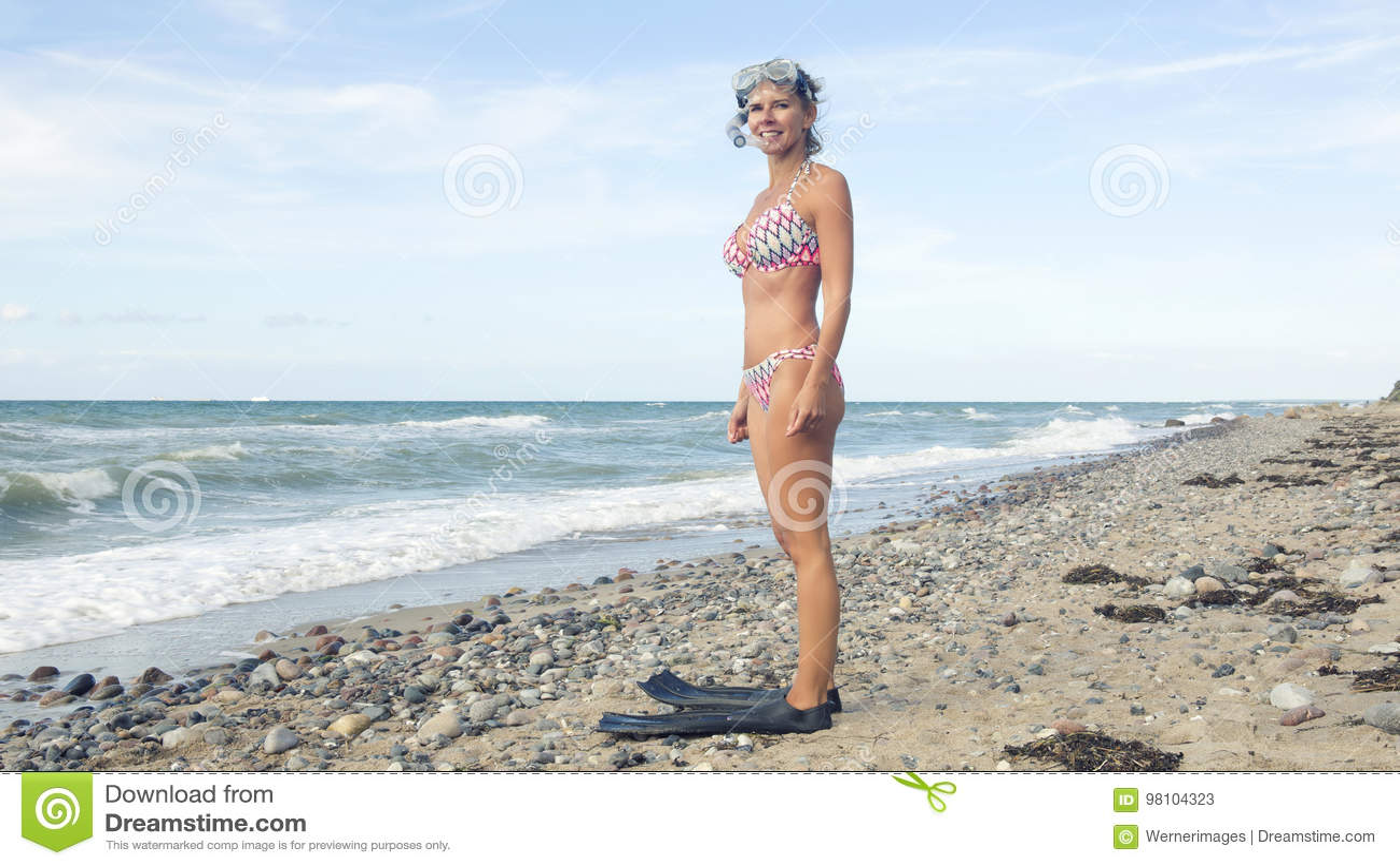 Frau im Bikini, der am Strand mit Schwimmenschutzbrillen steht