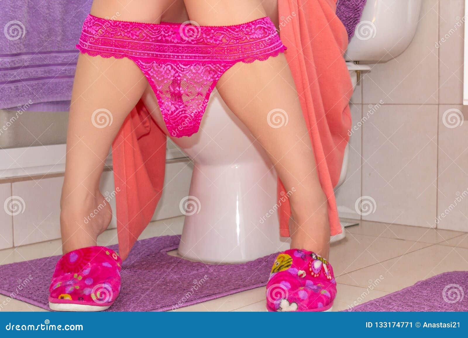 Frau im Hausmantel und in den Pantoffeln in der Toilette Getont nah herauf Bild sexy Junge mit dem Schlüpfer gefalteten Sitzen au