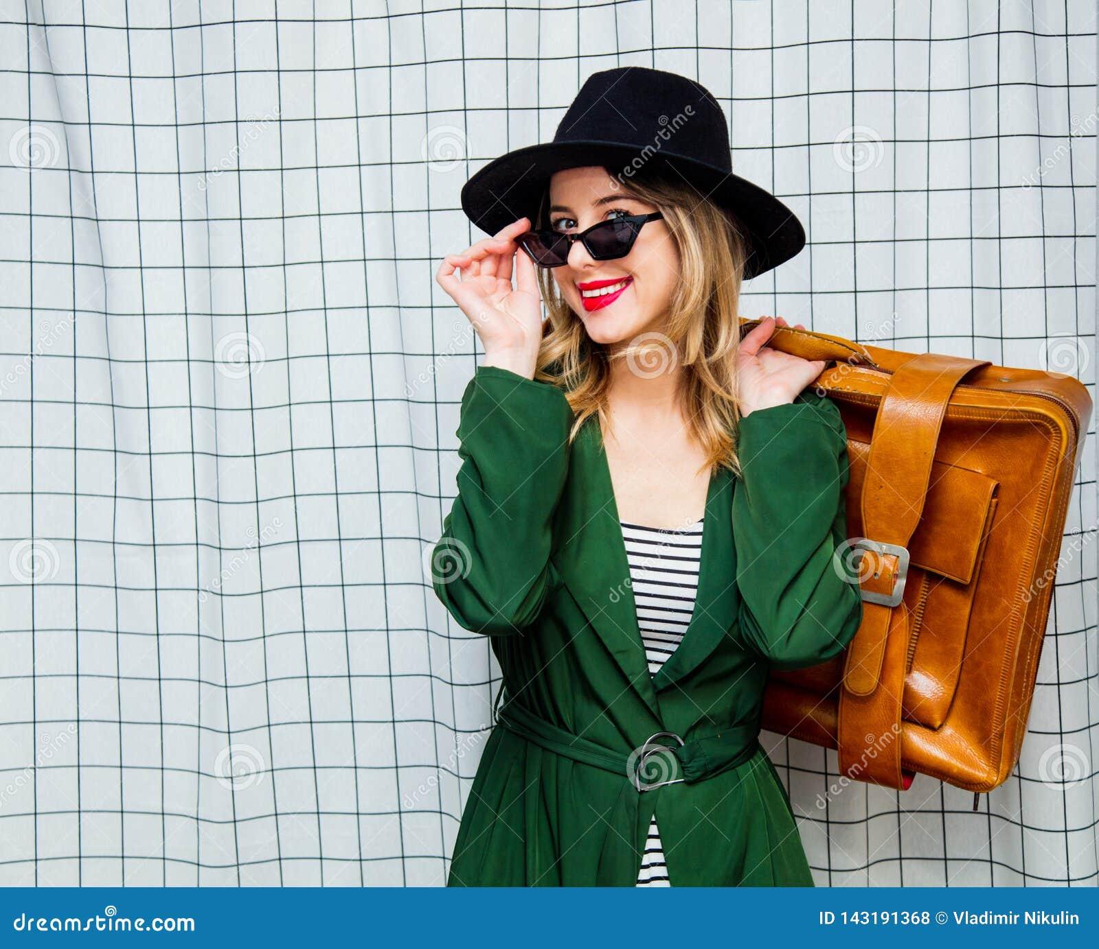 Frau im Hut und im grünen Mantel in der Art 90s mit Reisekoffer