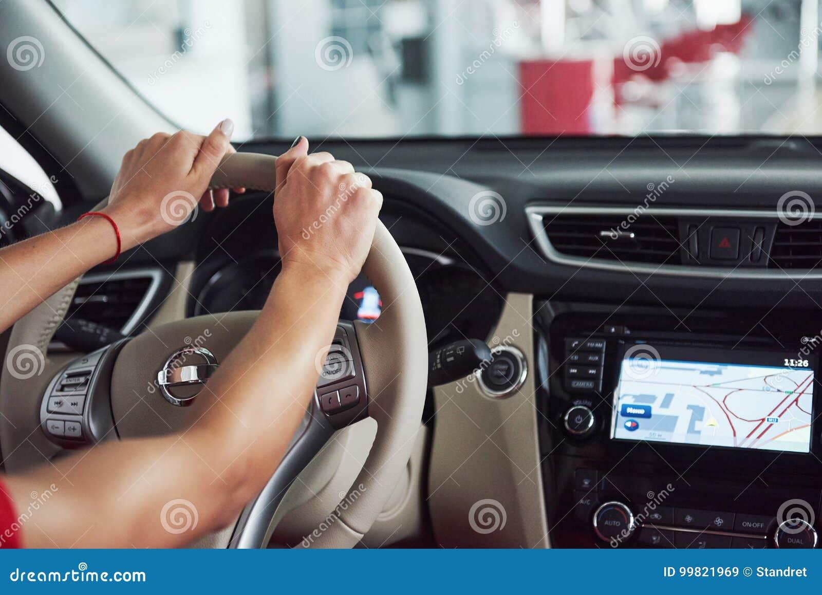 Frau im Innen Auto hält Rad, um lächelnde schauende Passagiere im Rücksitzideen-Taxifahrer gegen sich zu wenden