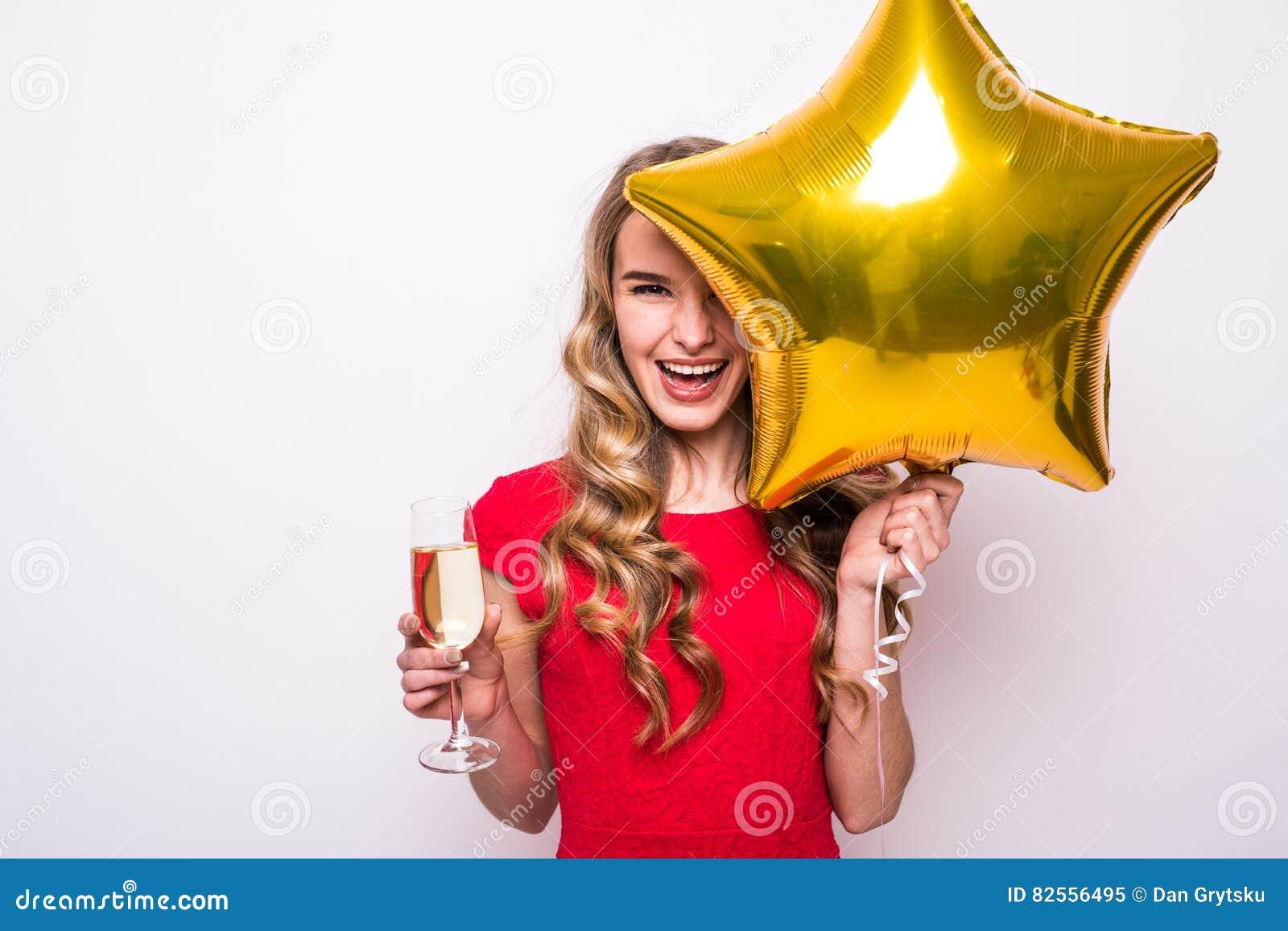 Frau im roten Kleid mit lächelndem und trinkendem Champagner des Goldsternförmigem Ballons