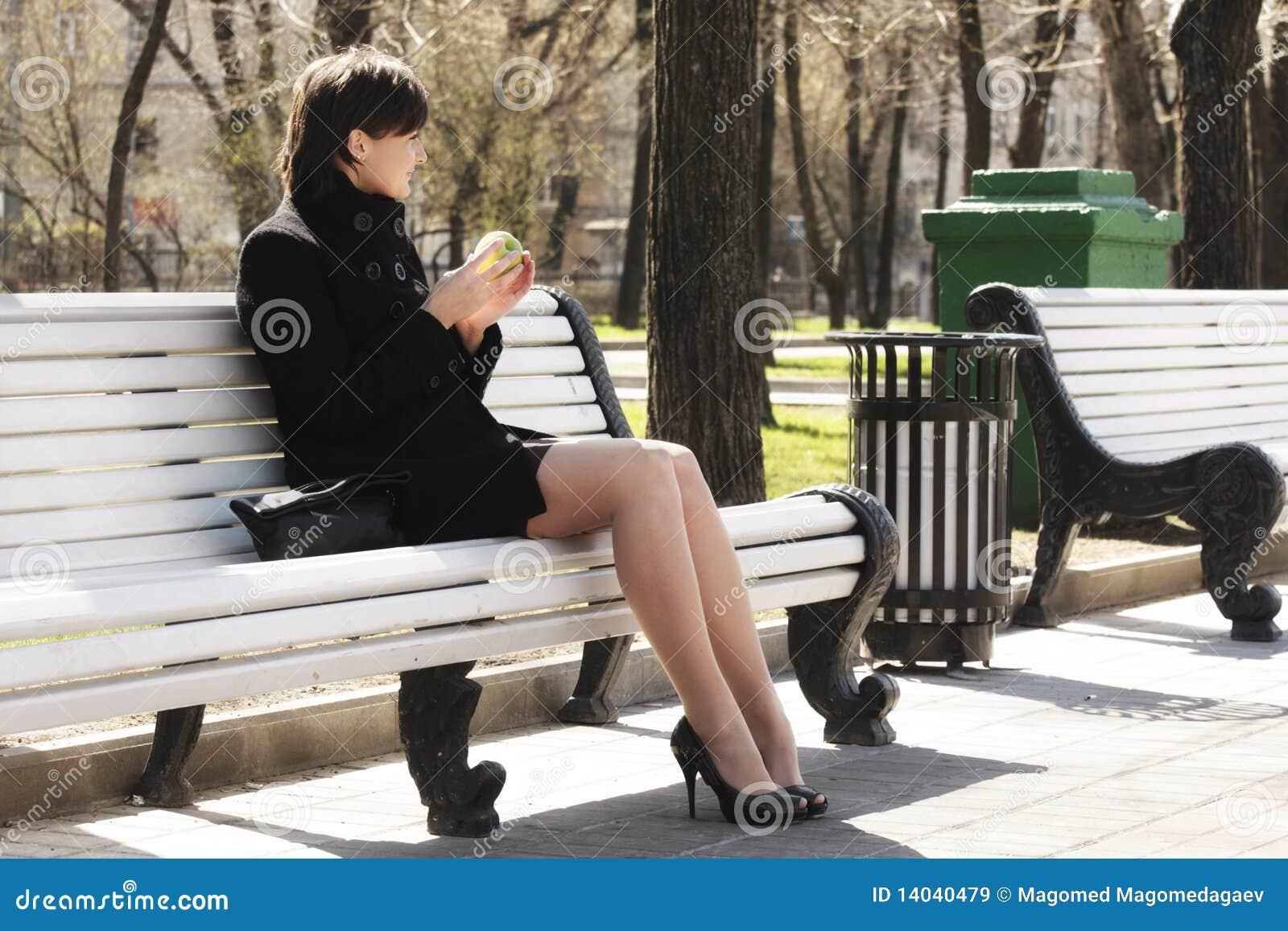 Frau im Schwarzen mit Apfel auf Bank