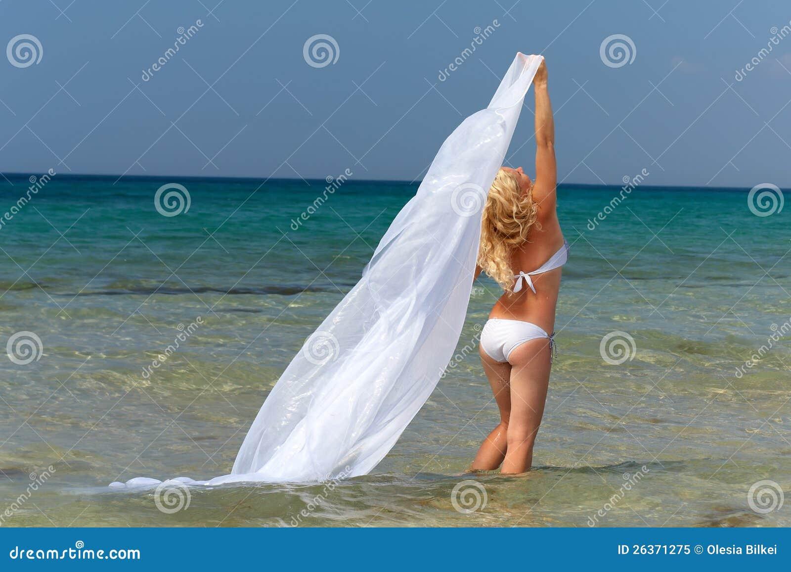 Frau im weißen Badeanzug und in der Feder im Meerwasser
