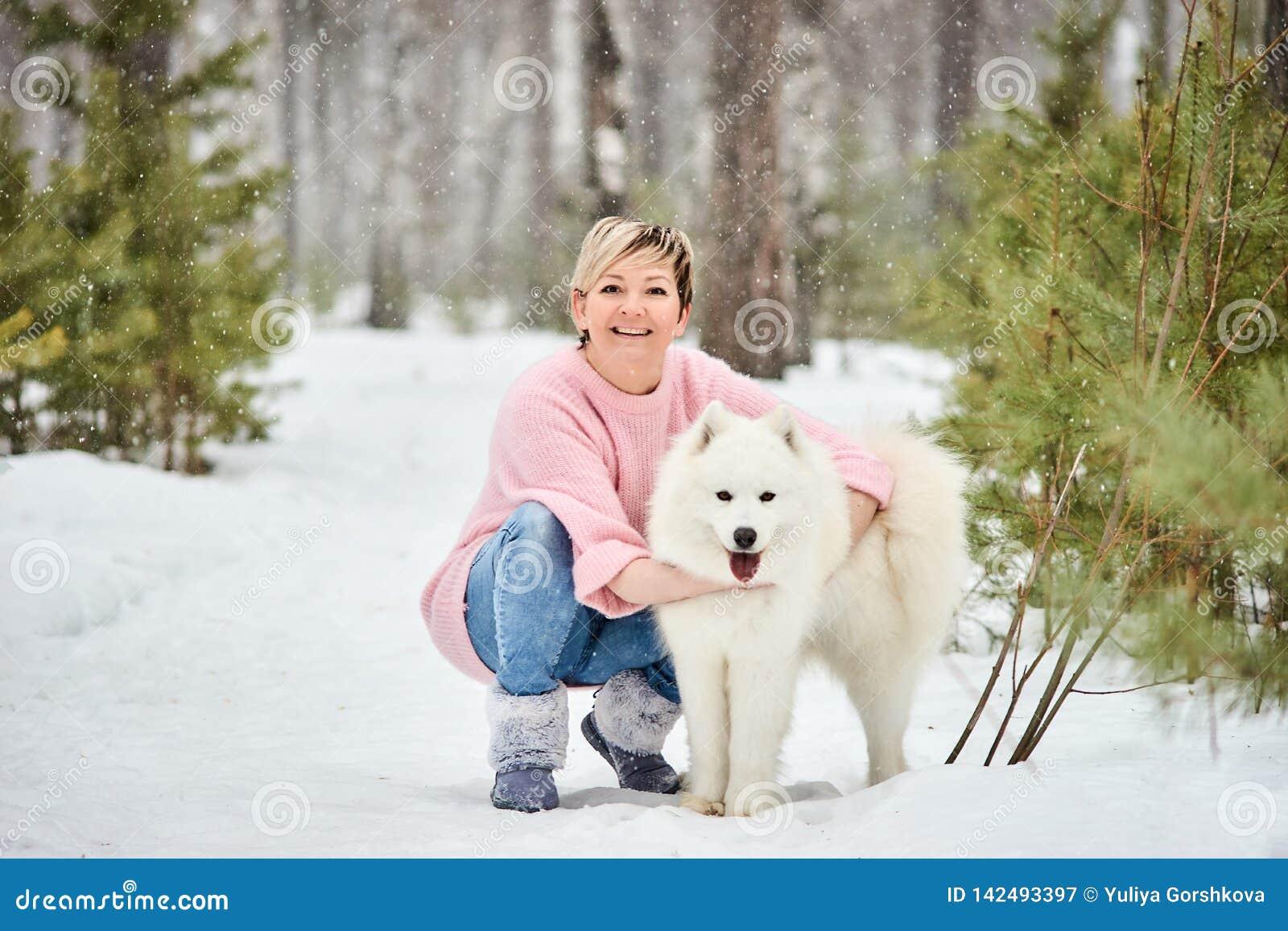 Frau im Winterwald gehend mit einem Hund Hinter den Paaren, Möbeln mit einem altmodischen Funk und einer Schwarzweiss-Fotografie