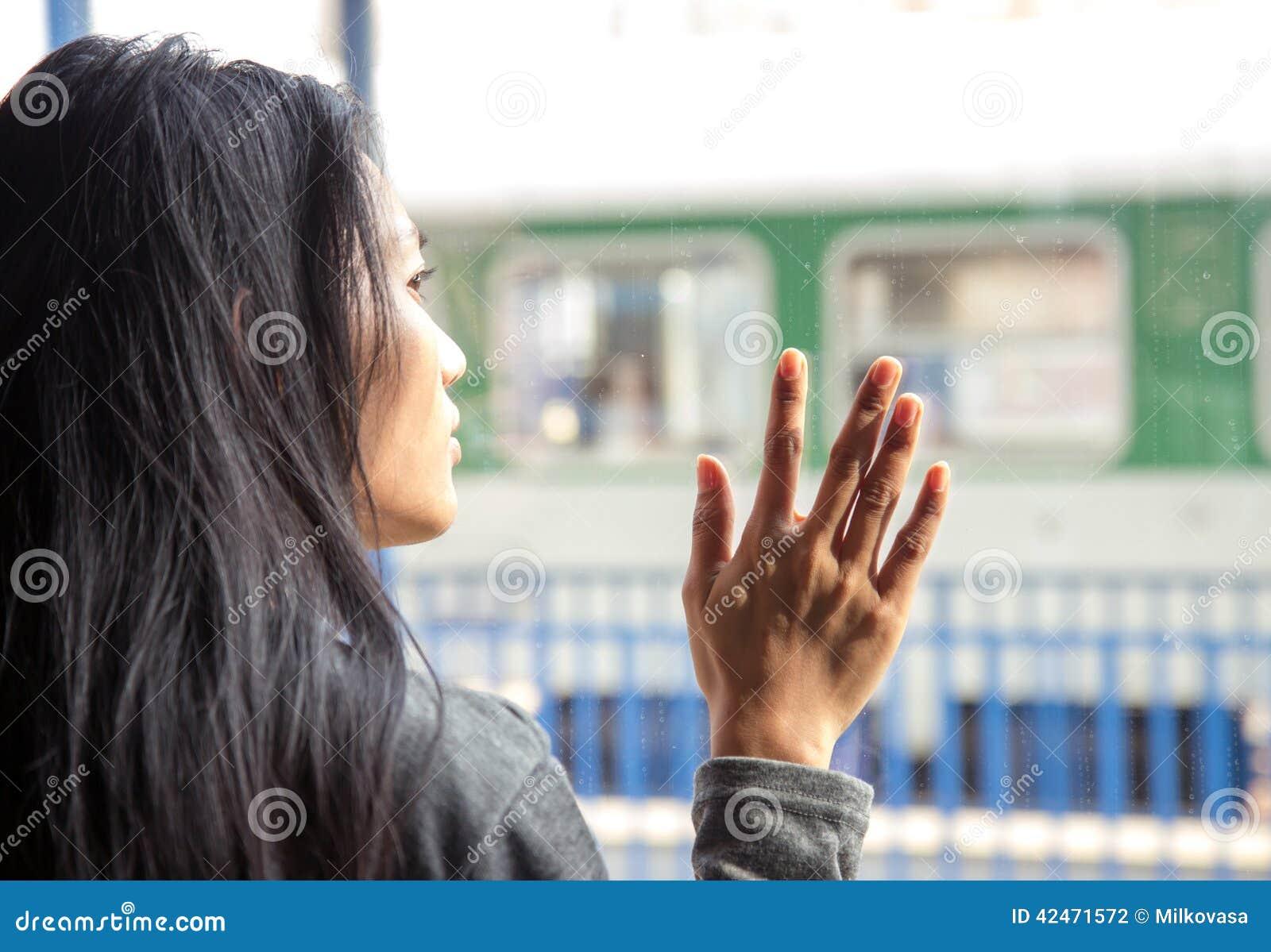 Frau im Zug, die heraus das Fenster schaut