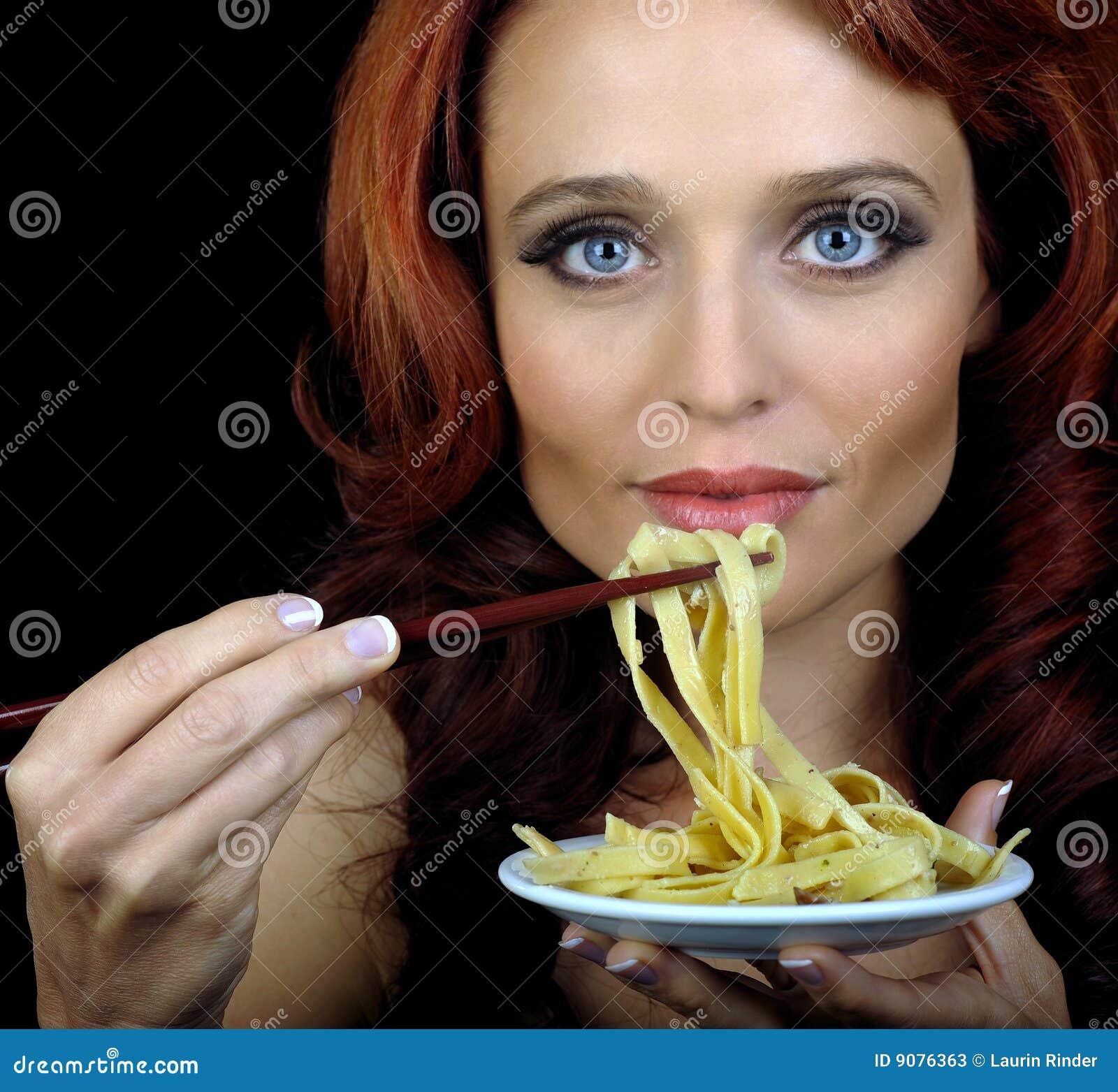 Frau isst Teigwaren