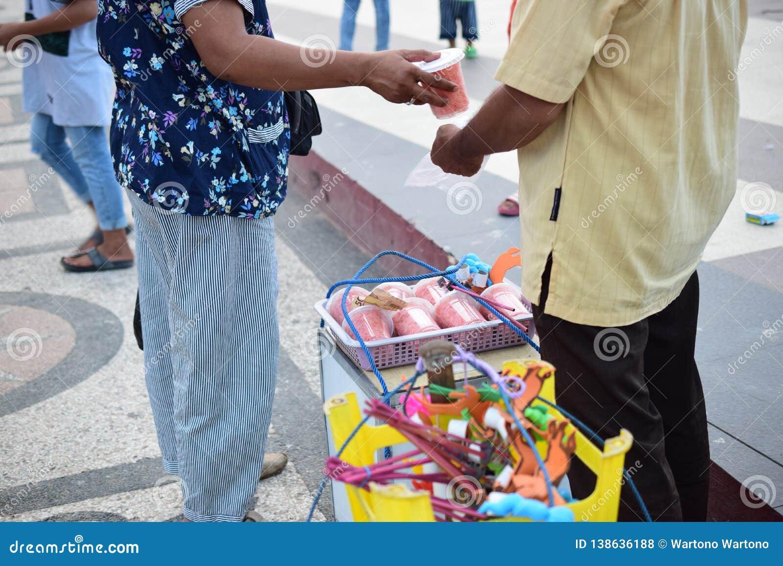 Frau kauft Zuckerwatte zu einem traditionellen Verkäufer