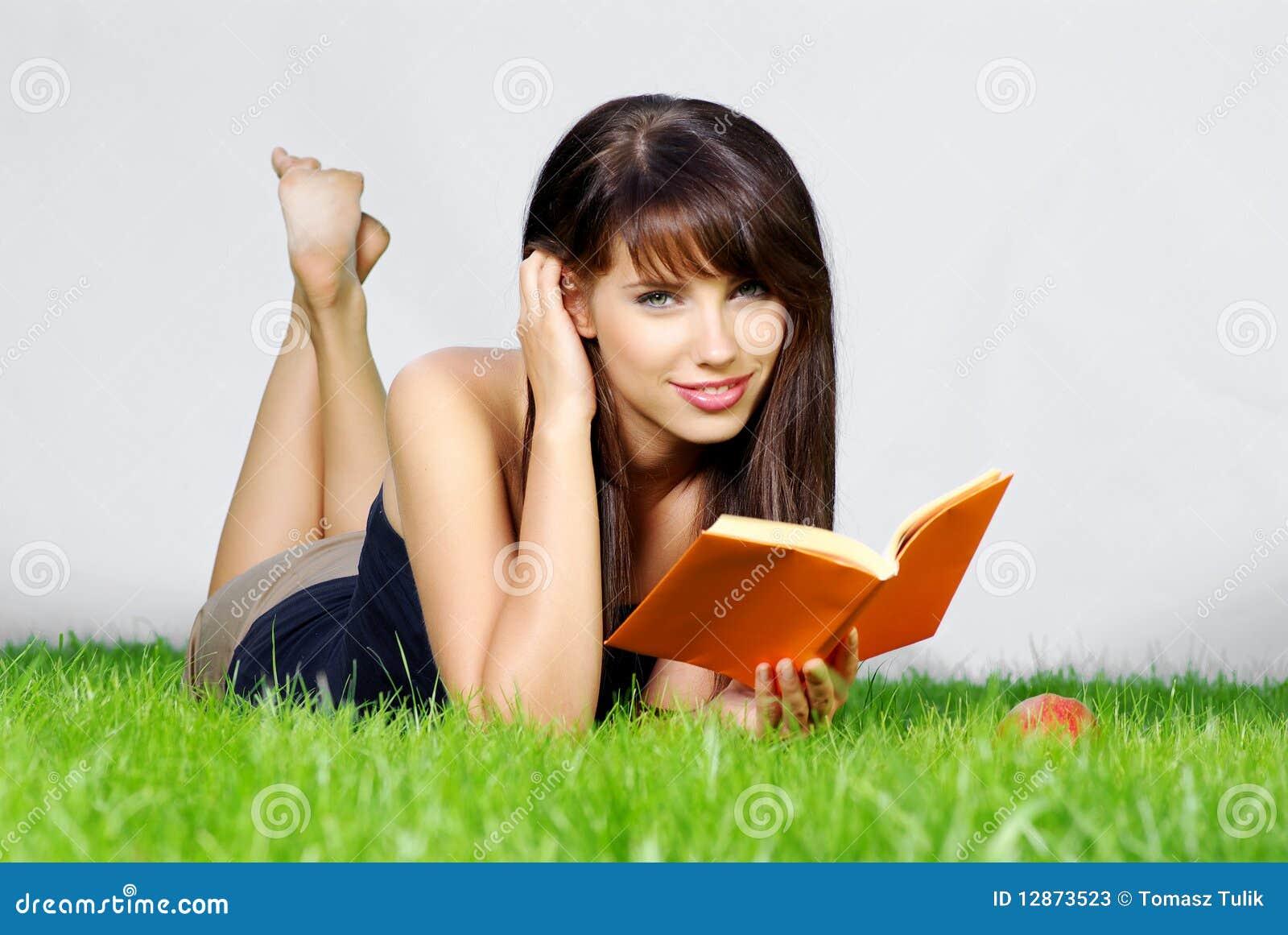 Frau legt auf grünes Feld und liest Buch.
