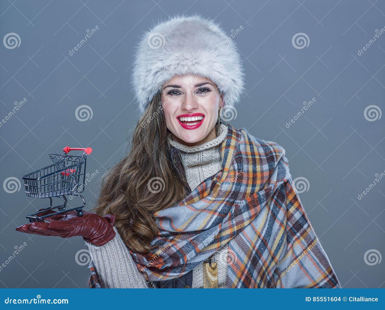 Frau lokalisiert auf dem kalten blauen Hintergrund, der Einkaufslaufkatze zeigt