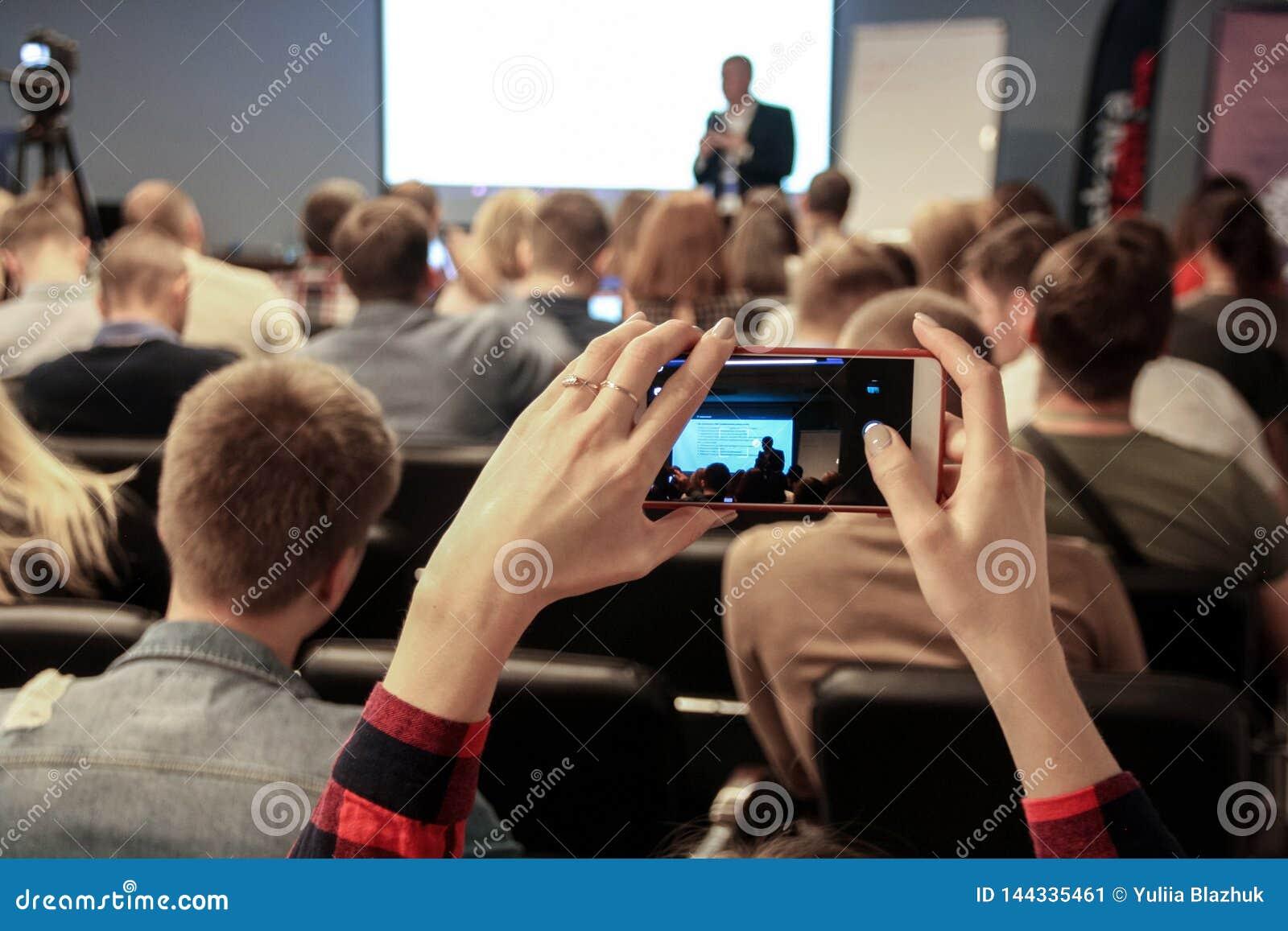 Frau macht ein Foto während der Konferenz unter Verwendung des Smartphone