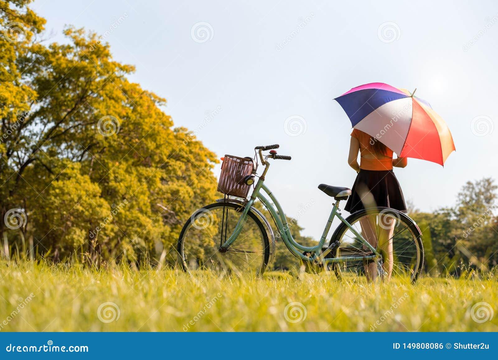 Frau mit colrful Regenschirm und Fahrrad im Park Leute und Entspannungskonzept Jahreszeit- und Herbstthema