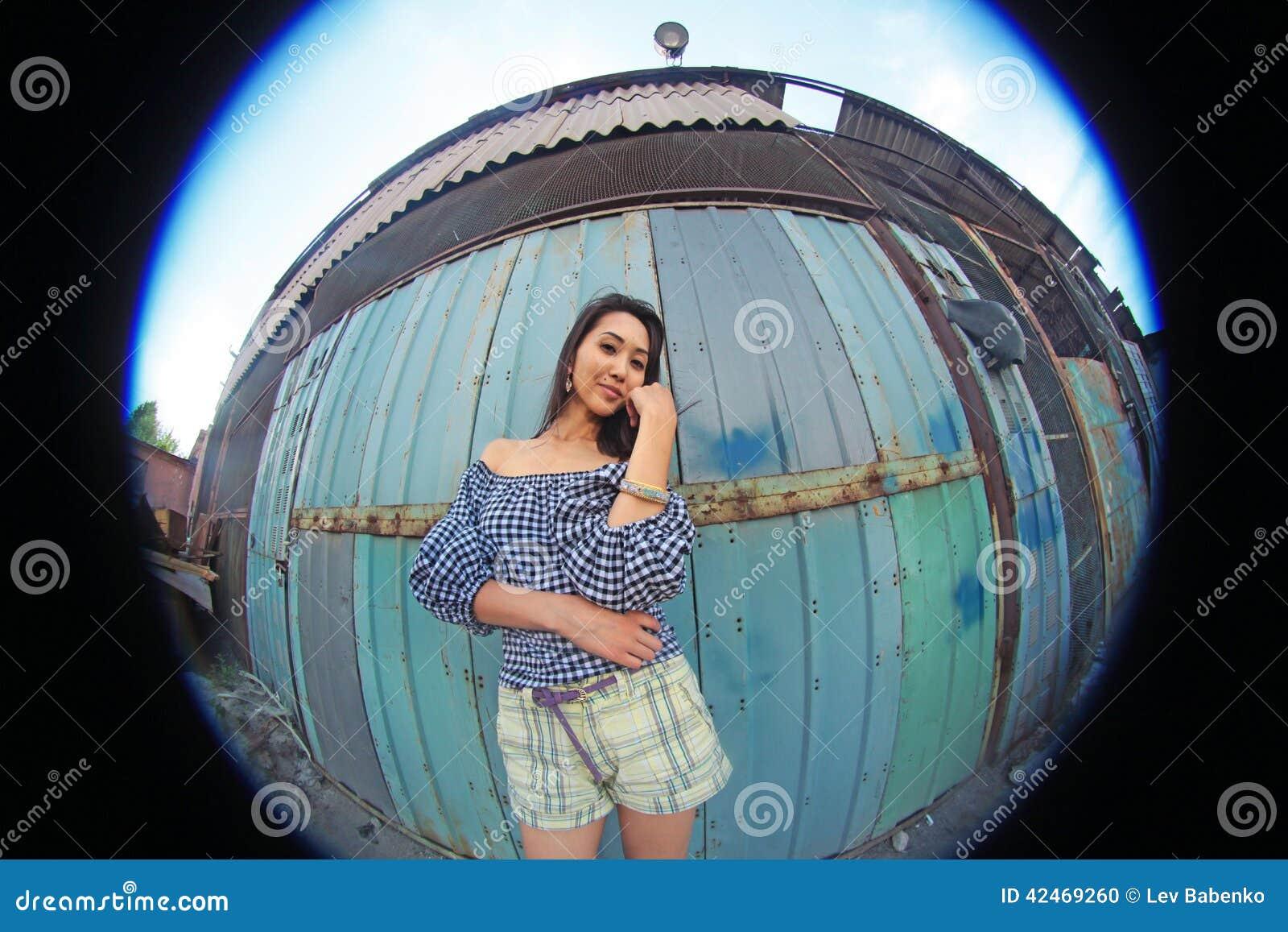 Frau mit dem lang flüssigen braunen Haar, das auf einem Hintergrund des alten rostigen Behälters, fisheye aufwirft