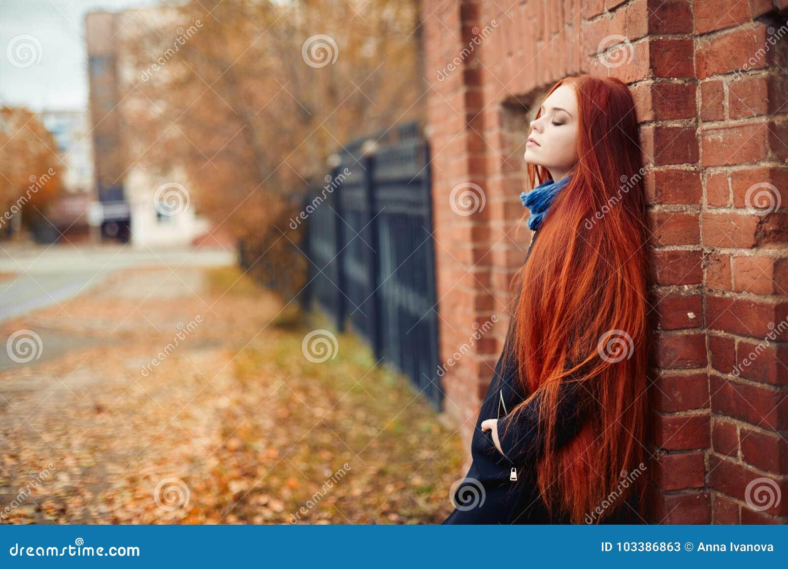 Frau mit dem langen roten Haar geht in Herbst auf der Straße Mysteriöser träumerischer Blick und das Bild des Mädchens Rothaarige
