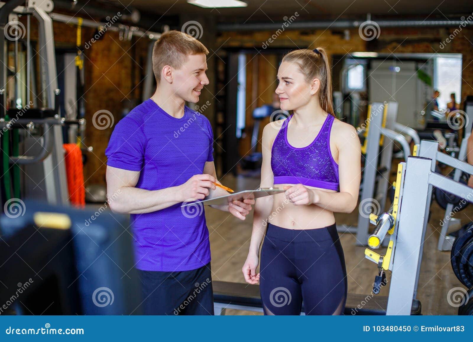 Frau mit dem persönlichen Trainer, der Trainingsplan in der Turnhalle erstellt