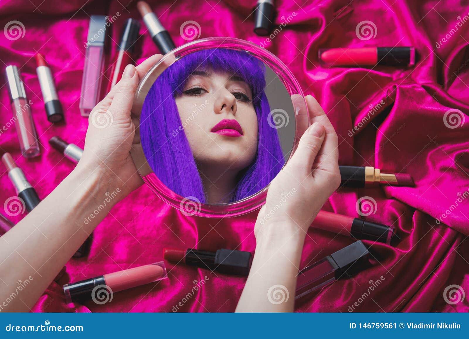 Frau mit dem purpurroten Haar, das in einem Spiegel mit Kosmetik schaut