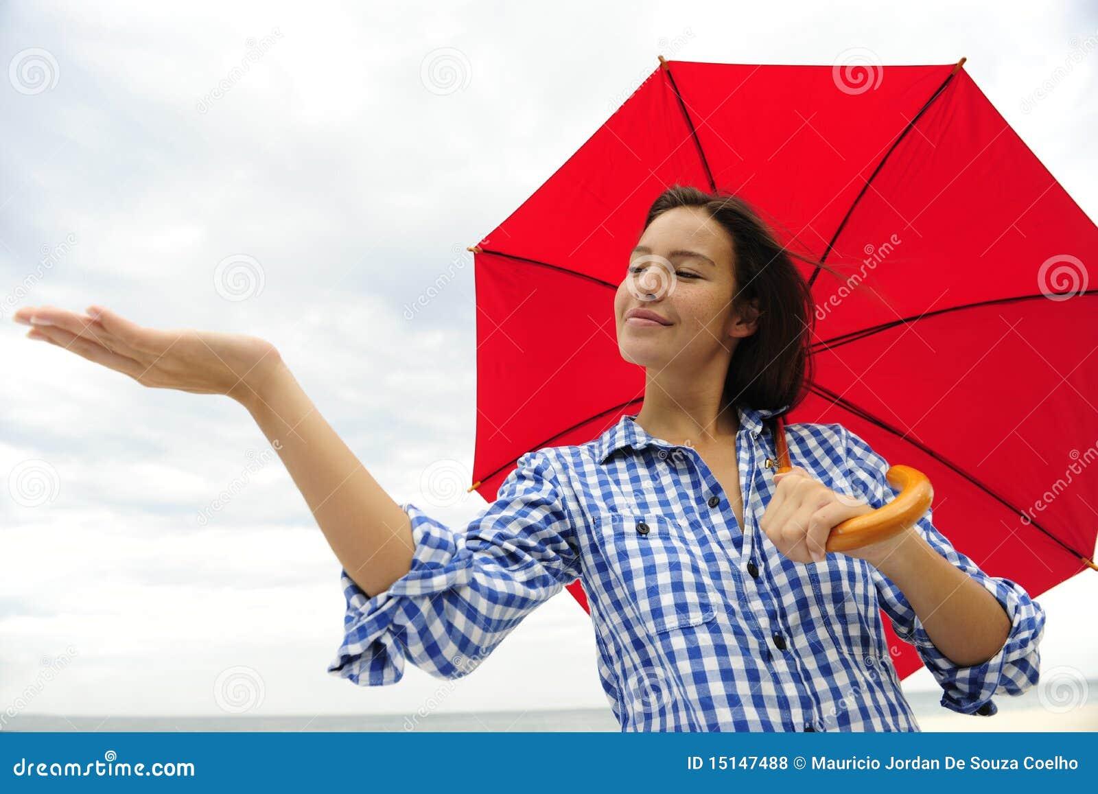 Frau mit dem roten Regenschirm, der den Regen berührt