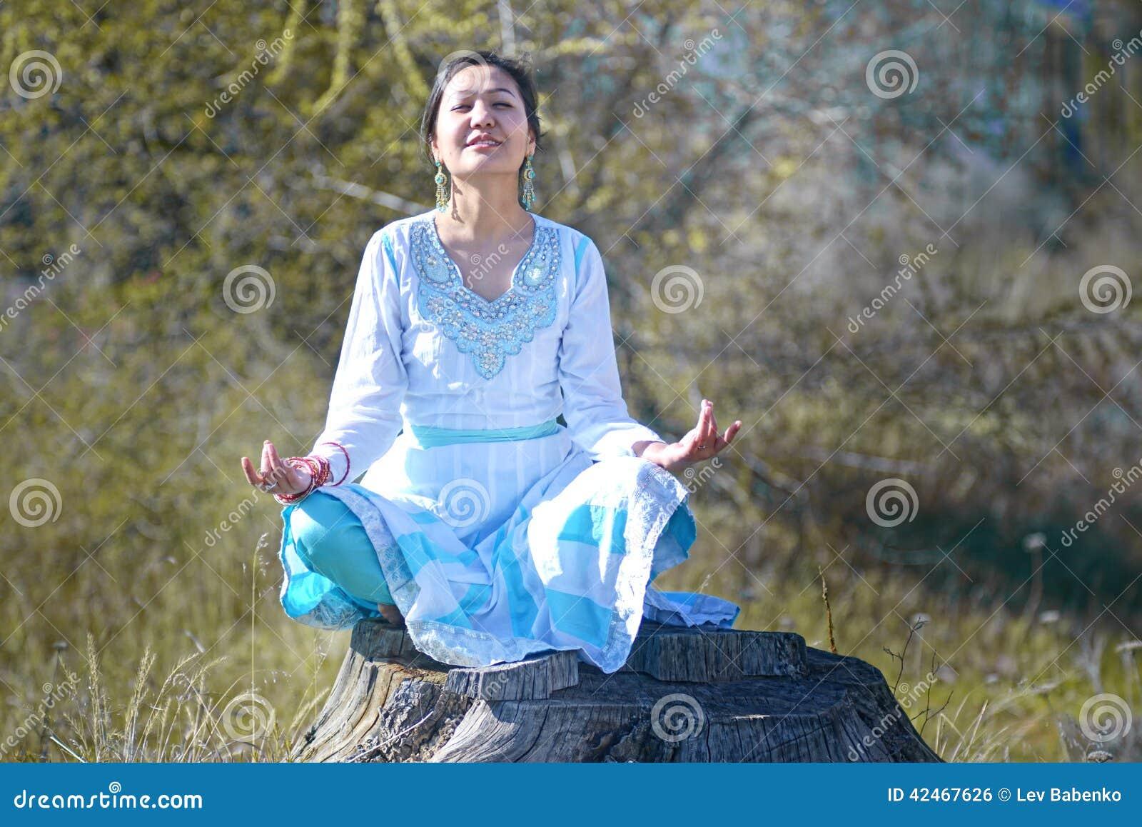 Frau mit dem schwarzen Haar im blauen Sari, auf der Natur im Holz