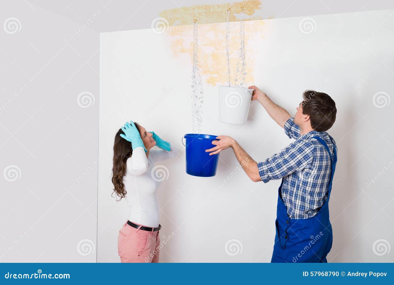 frau mit der arbeitskraft die wasser von der decke im eimer sammelt stockfoto bild von. Black Bedroom Furniture Sets. Home Design Ideas