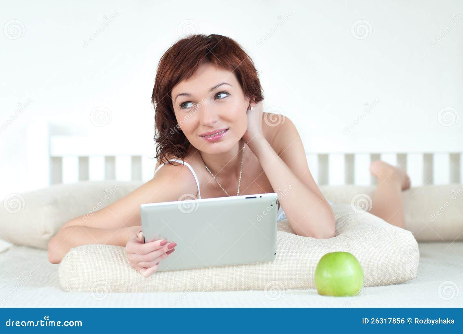 Frau mit einem grünen Apfel und Tablette am Bett