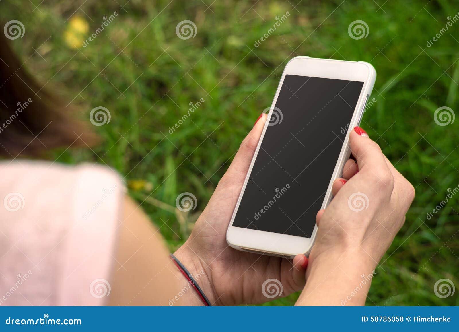 Frau mit einem Telefon in seiner Hand