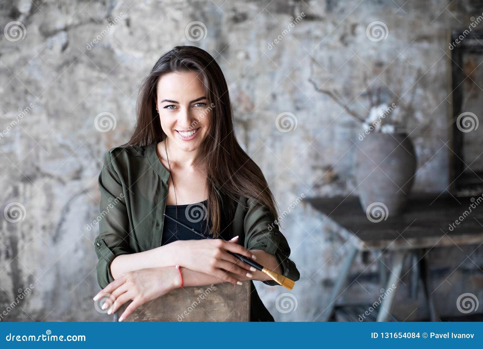 Frau mit einer Bürste in ihrer Hand und in einem reizend Lächeln auf ihrem Gesicht fotografierte Sitzen auf einem Stuhl in einem