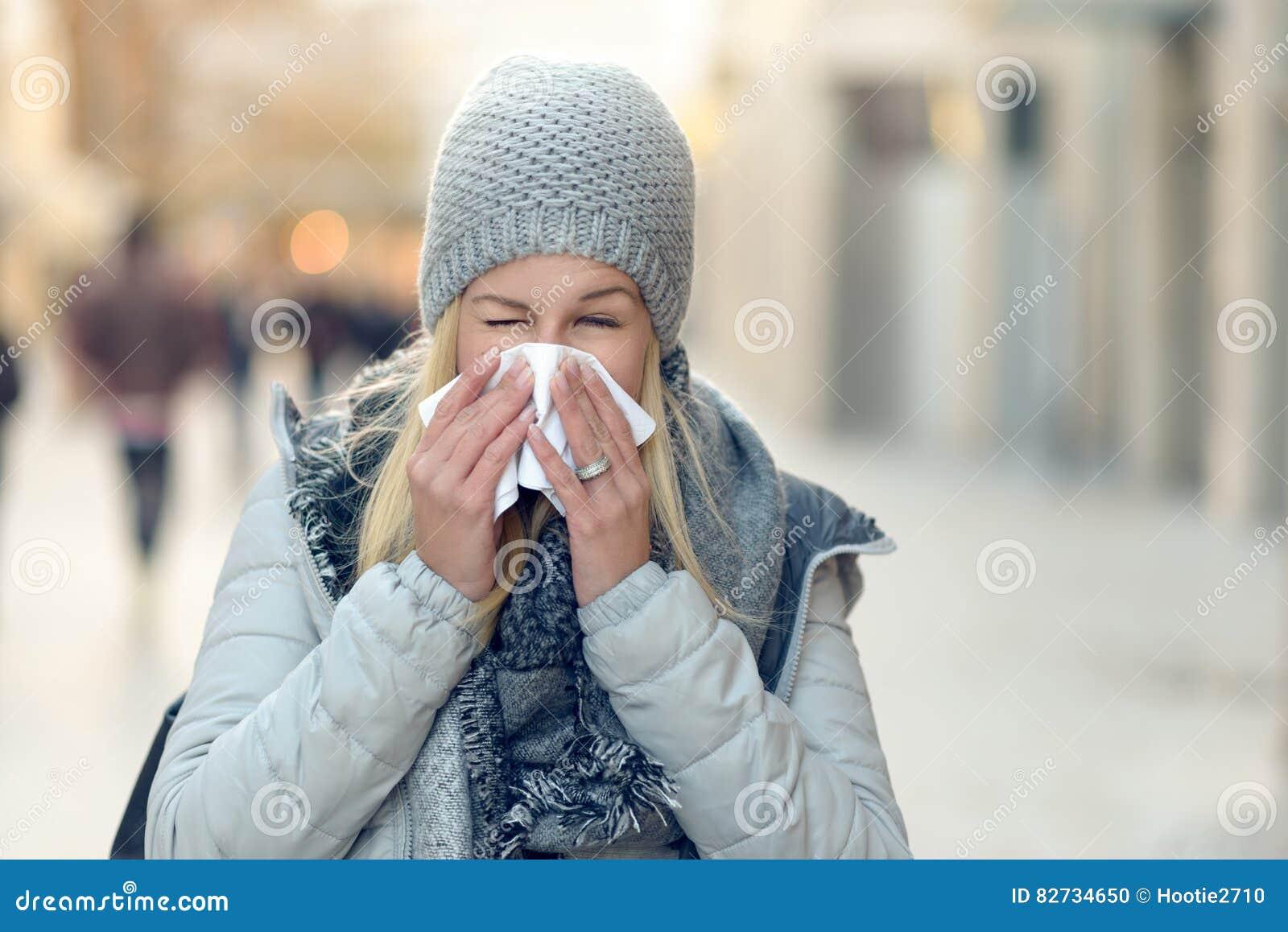 Frau mit einer Saisonwinterkälte, die ihre Nase durchbrennt