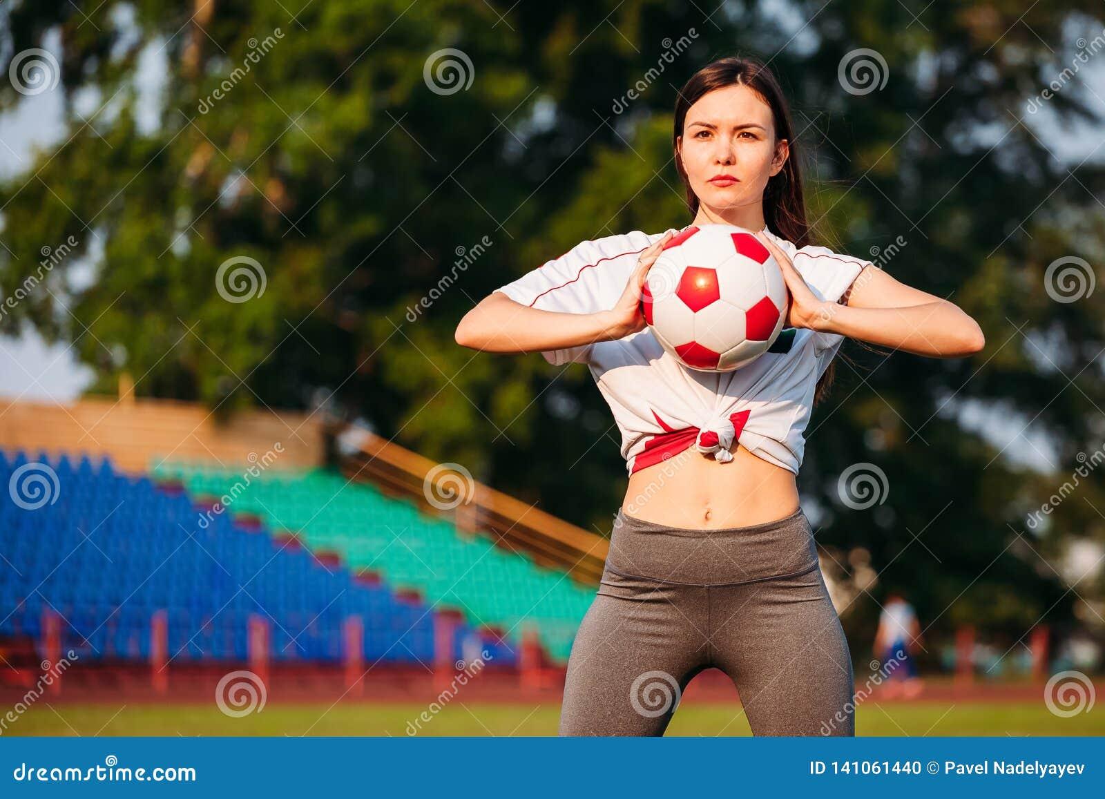 Frau mit Fußball in ihren Händen auf Fußballplatz auf Hintergrund von Ständen