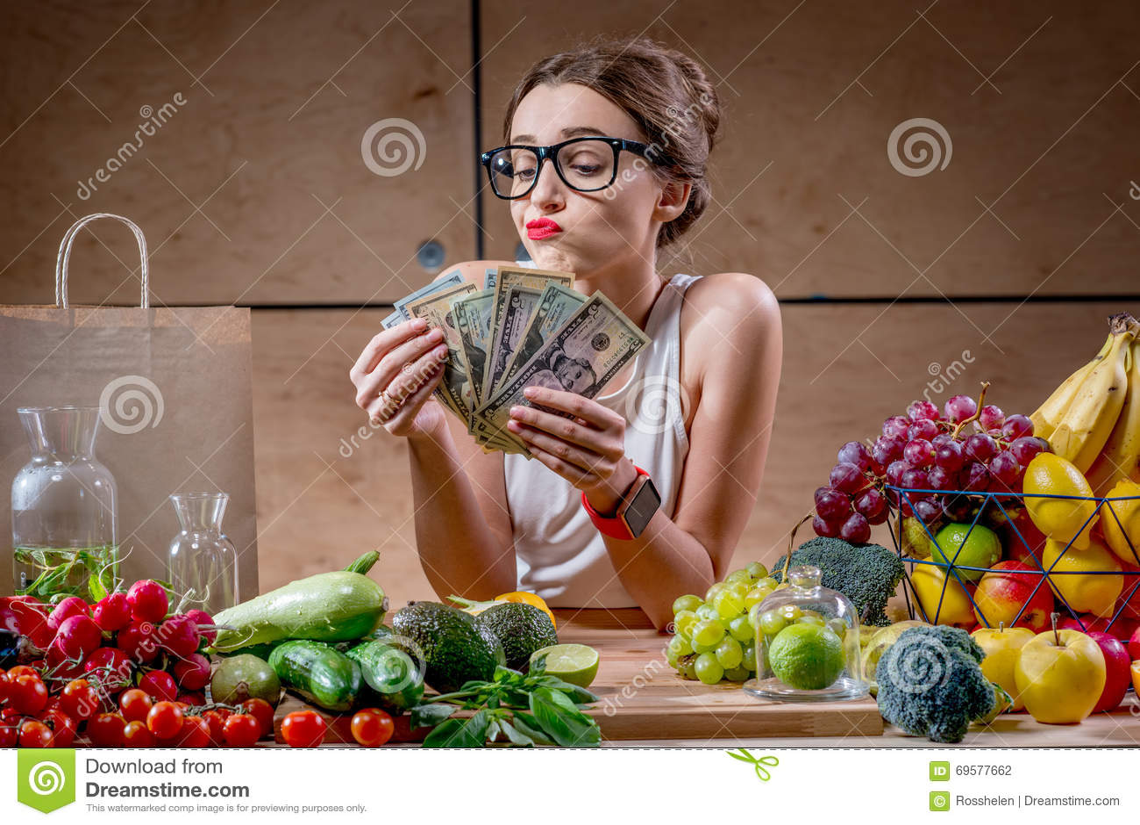 Frau mit Geldbargeld und gesundem Lebensmittel