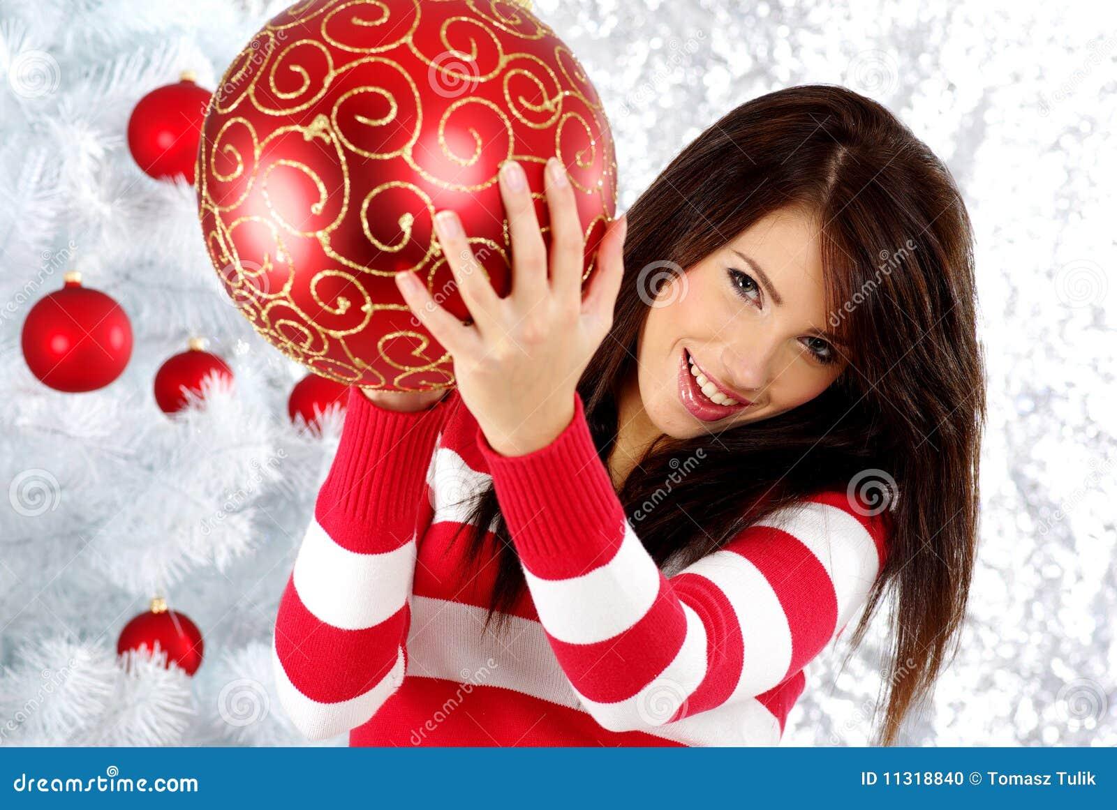 Frau mit Geschenk nahe bei weißem Weihnachtsbaum