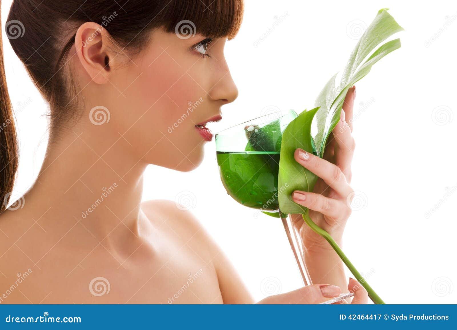 Frau mit grünem Blatt und Glas Wasser